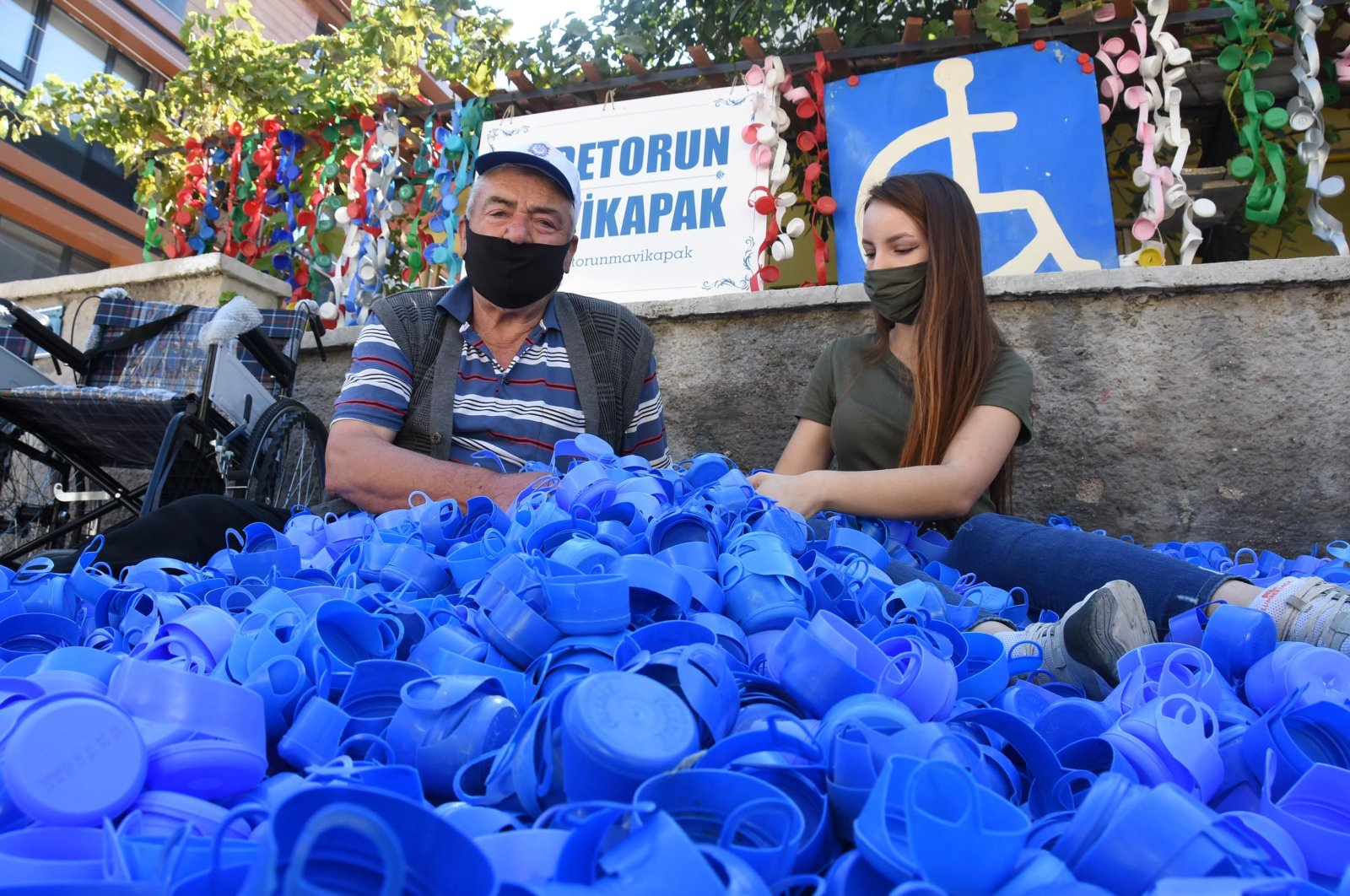 Halit Aydoğan (L) and his granddaughter Melike Sarıtaş pose with lids they collected and wheelchairs they bought, in Eskişehir, central Turkey, Sept. 13, 2020. (DHA Photo)
