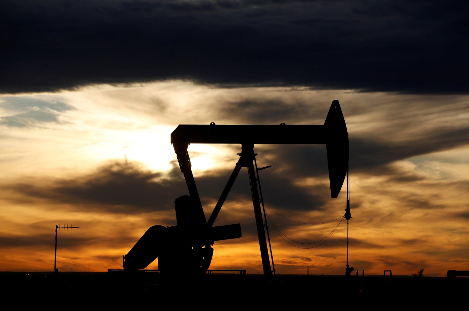 The sun sets behind a crude oil pump jack on a drill pad in the Permian Basin in Loving County, Texas, Nov. 24, 2019. (Reuters Photo)