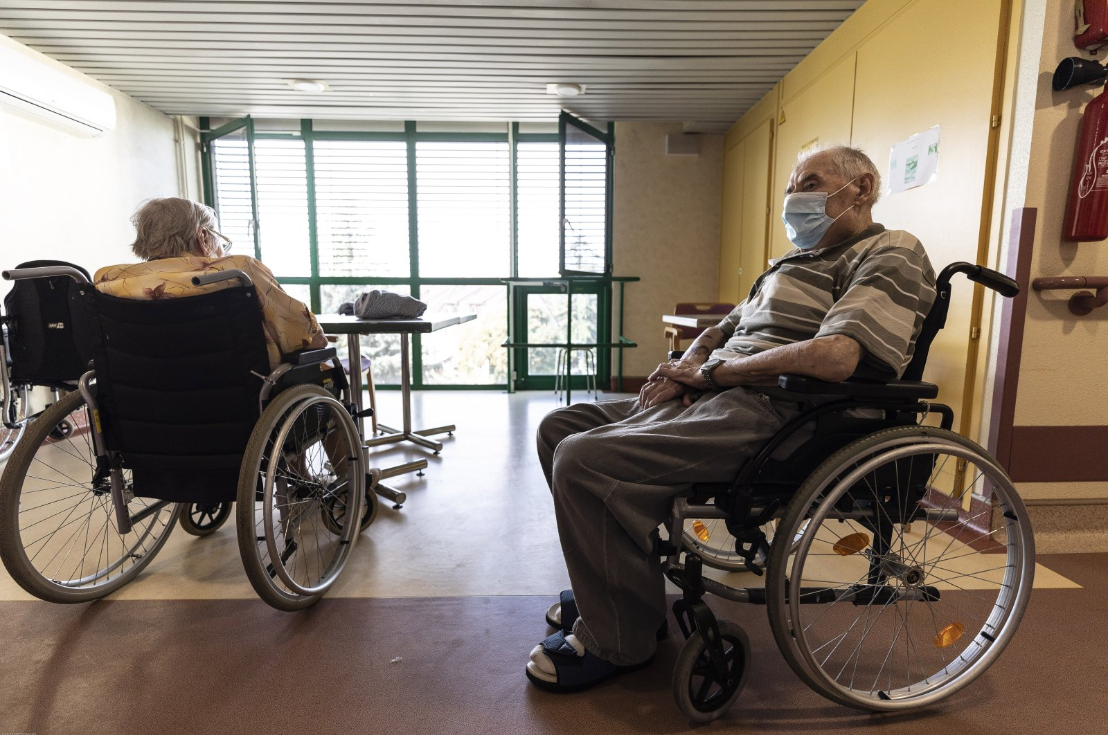 Elderly people in wheelchairs sit at a nursing home in Strasbourg, France, Aug. 19, 2020. (AP Photo)