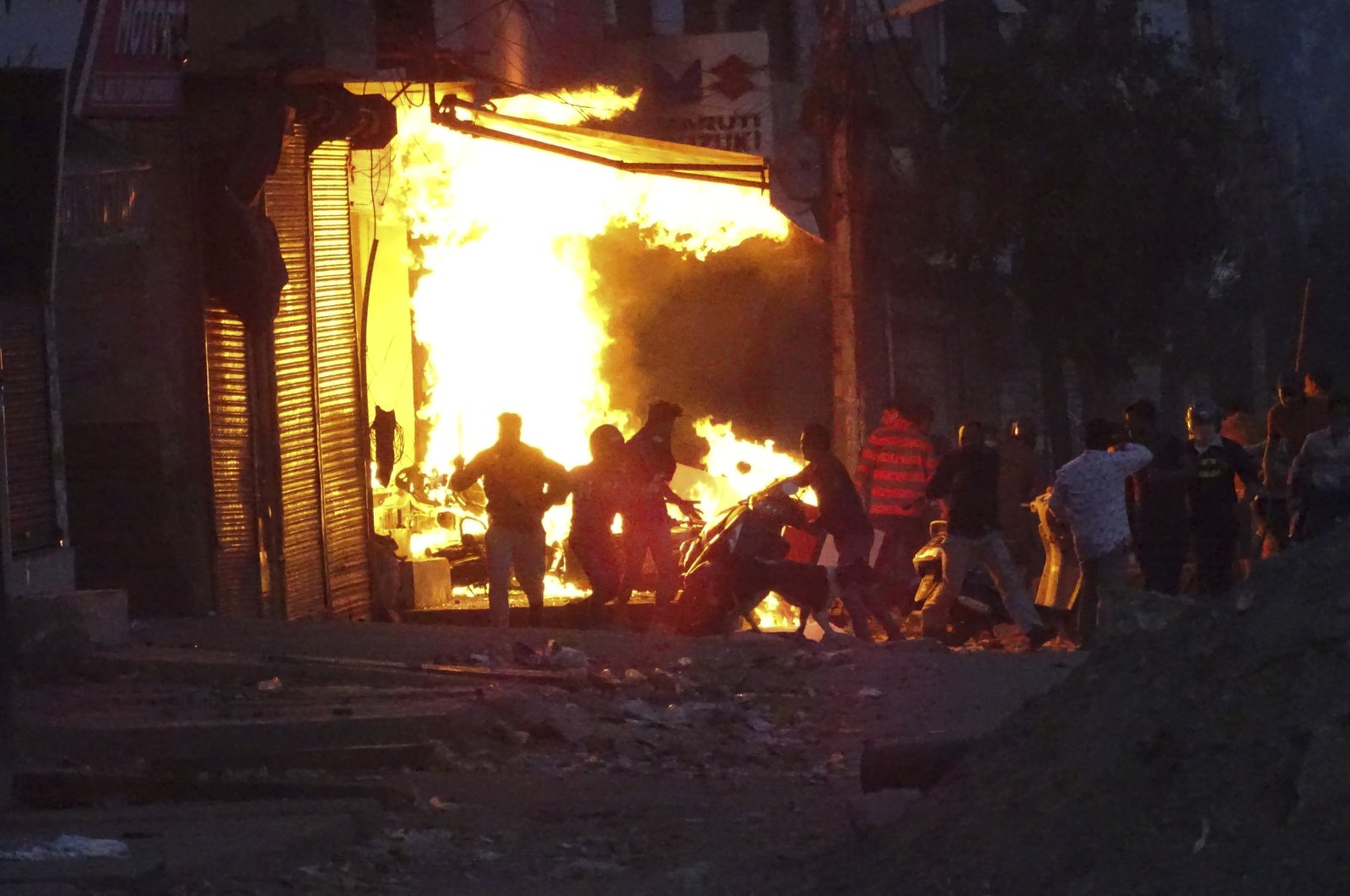 In this file photo, a shop burns after it was set on fire by a mob during deadly religious riots in New Delhi, India, Feb. 25, 2020. (AP Photo)