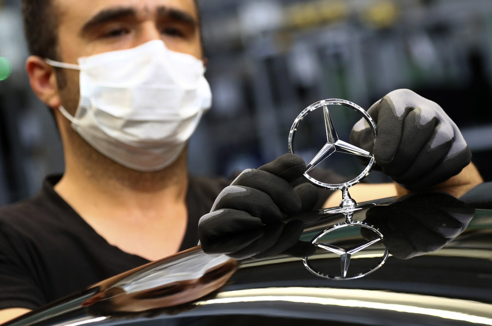 An employee wearing a face mask attaches a Mercedes emblem as he works on an S-class car at the Mercedes plant in Sindelfingen, Germany, April 30, 2020. (AP Photo)