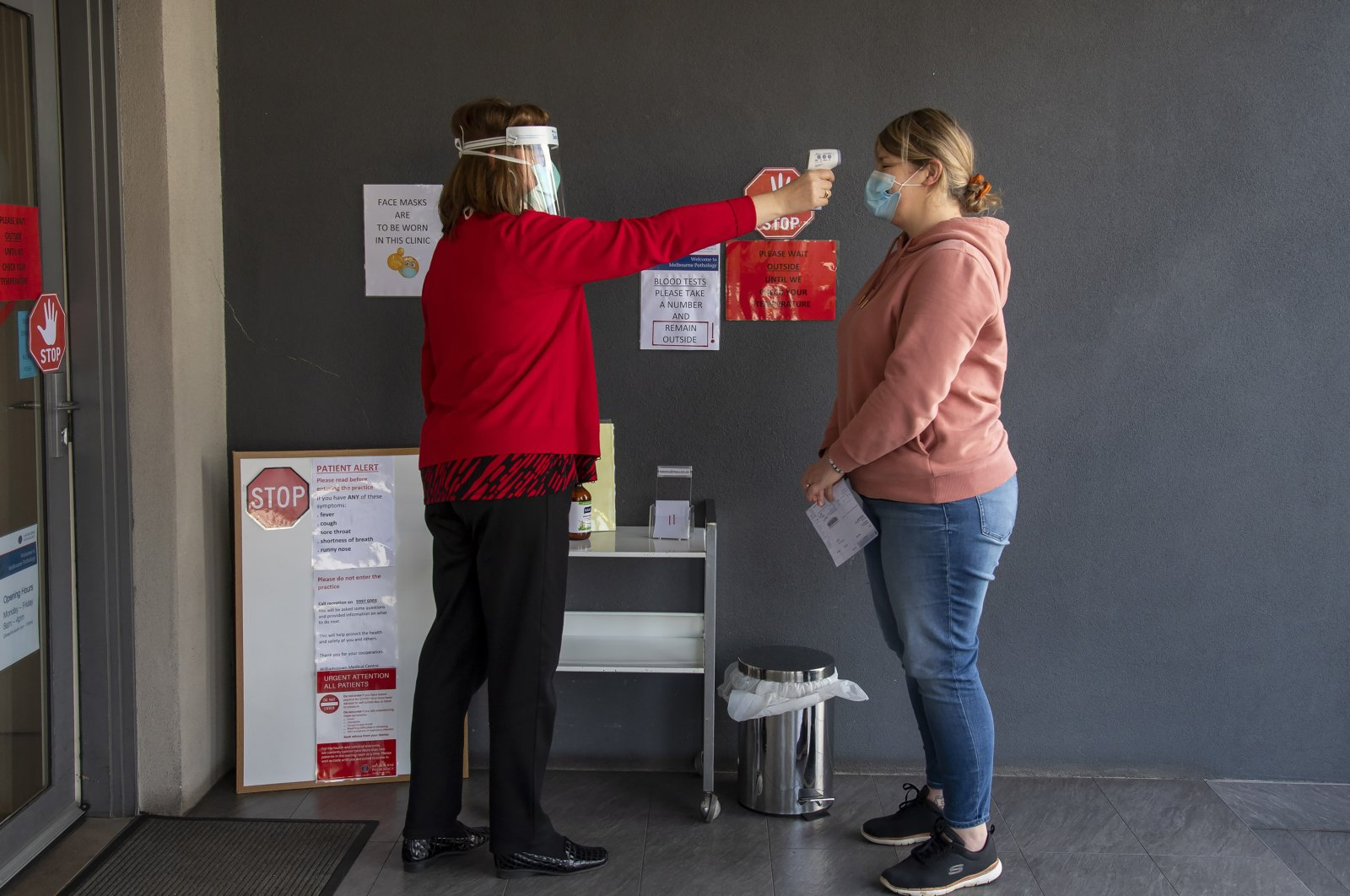 A patient has her temperature checked at a medical clinic during lockdown due to the continuing spread of the coronavirus in Melbourne, Aug. 6, 2020. (AP Photo)