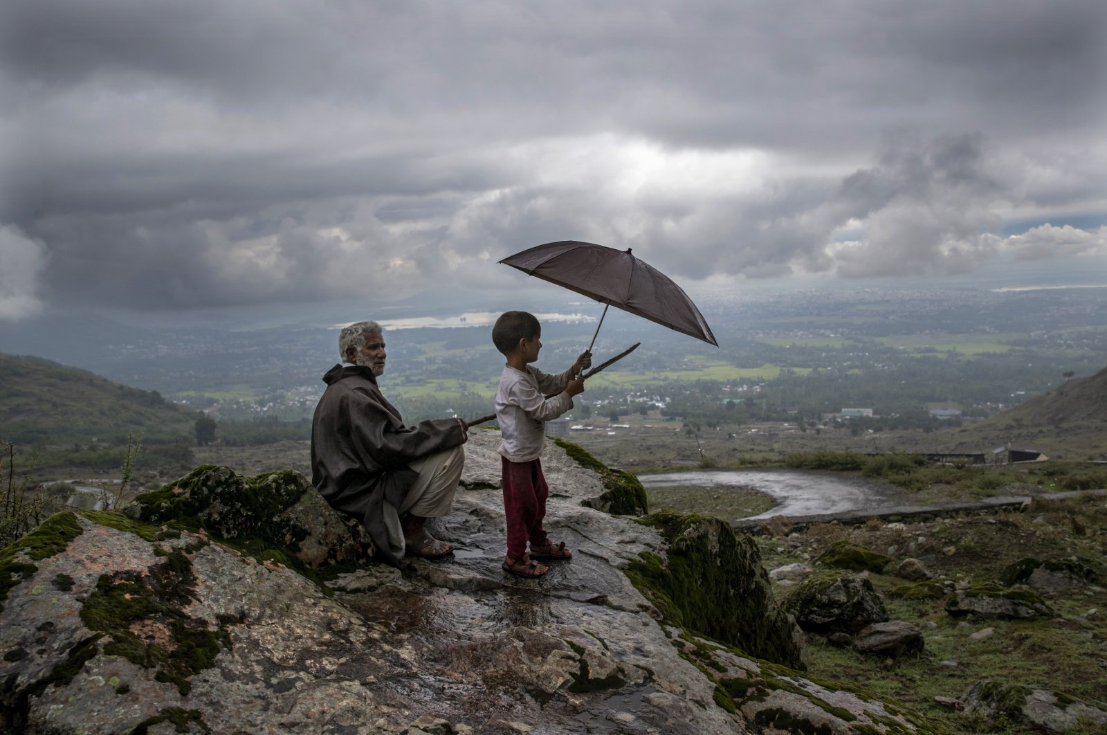 A Kashmiri villager with his grandson keeps watch over their cattle from a hillock on the outskirts of Srinagar, Indian-controlled Kashmir, Aug. 31, 2020. (AP Photo)