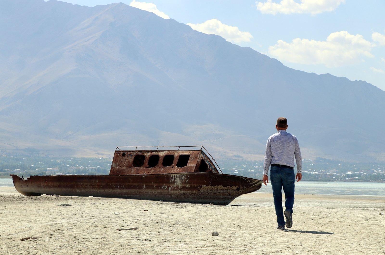 Professor Faruk Alaeddinoğlu of Van Yüzüncü Yıl University walks toward an old fishing boat that ran aground as water levels decreased in Lake Van, Van province, eastern Turkey, Sept. 15, 2020. (DHA Photo)