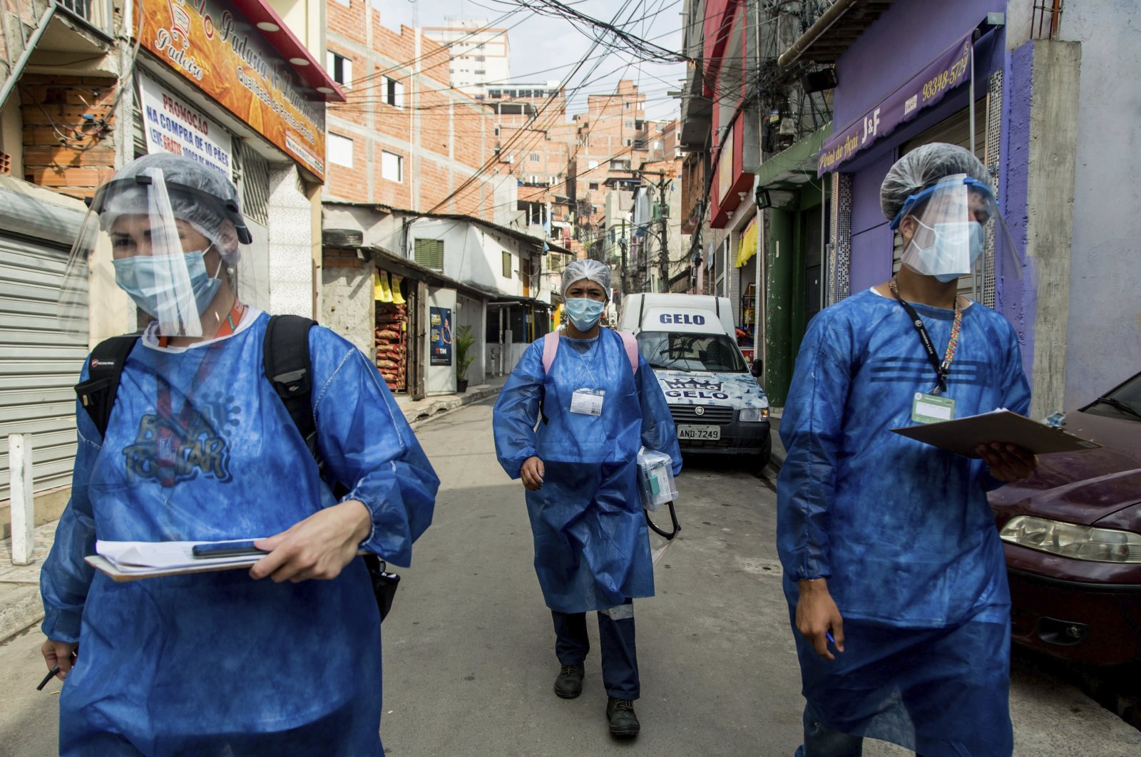 "Members of the ""Bora Testar"" or Let's Test project, walk through the the Paraisopolis neighborhood of Sao Paulo, Brazil, Sept. 11, 2020. (AP Photo)"