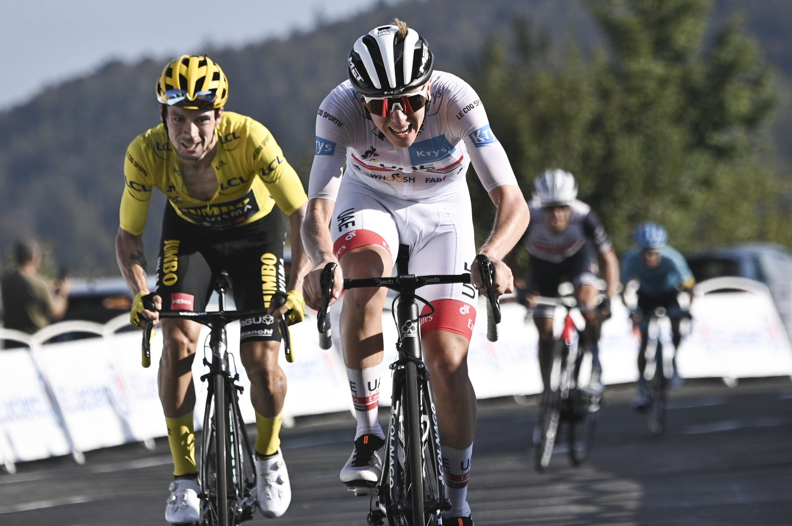 Slovenia's Tadej Pogacar (C) wins stage 15 of the Tour de France cycling race over 174.5 kilometers from Lyon to Grand Colombier pass, France, Sept. 13, 2020. (AP Photo)