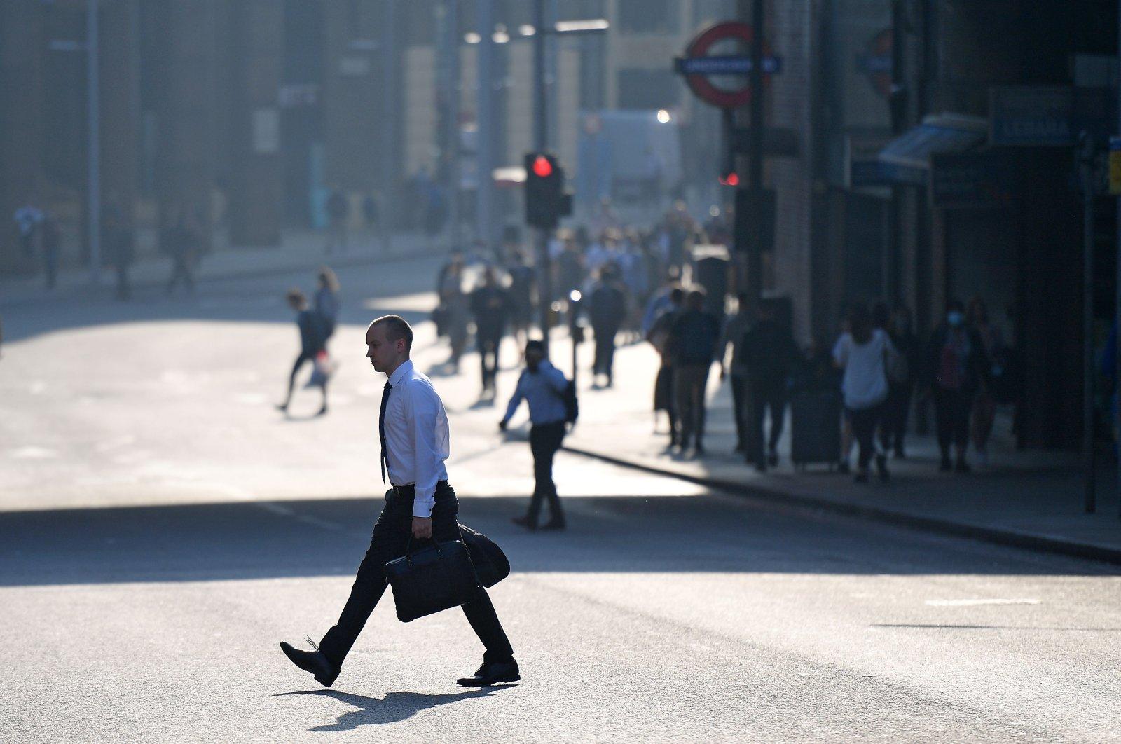 A commuter crosses a road by London Bridge in London, Britain, Sept. 15, 2020. (AFP Photo)