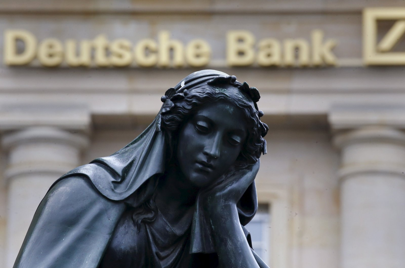 A statue is seen next to the logo of Germany's Deutsche Bank in Frankfurt, Germany, Jan. 26, 2016. (Reuters Photo)