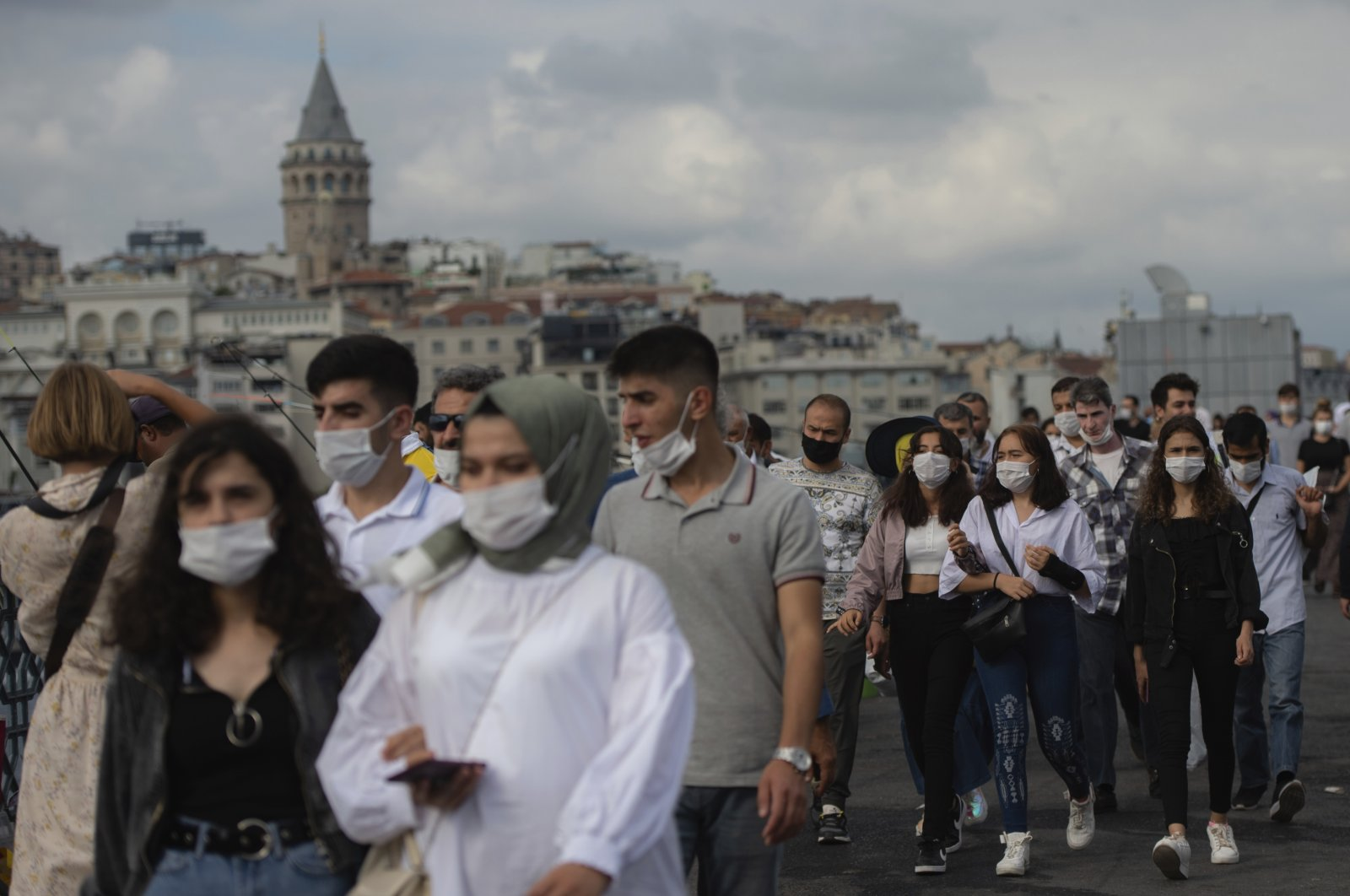 Backdropped by Istanbul's iconic Galata Tower, people wearing masks for protection against the spread of coronavirus, walk over Eminönü bridge in Istanbul, Friday, Sept. 11, 2020. (AP Photo)