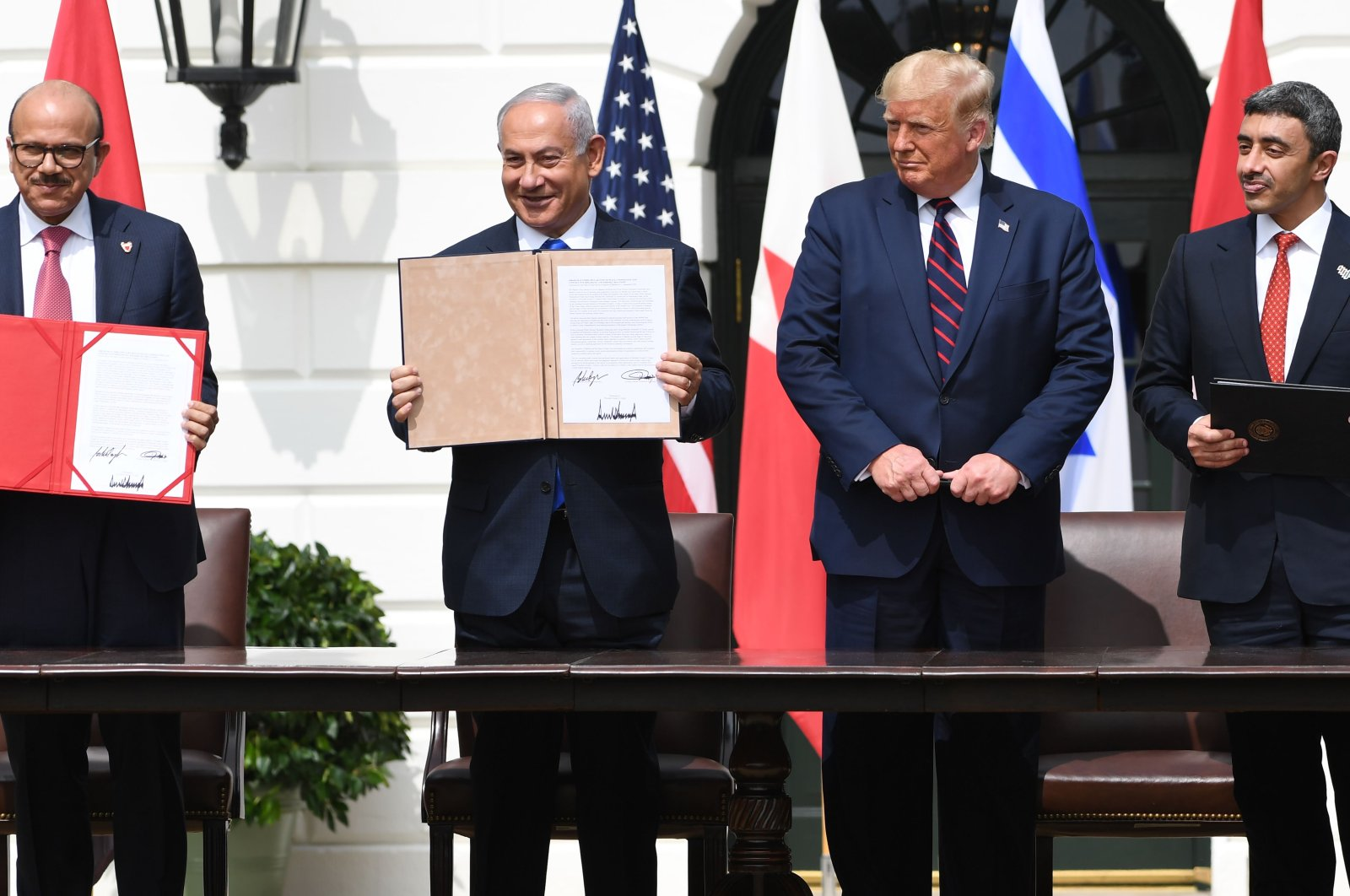 Bahraini Foreign Minister Abdullatif al-Zayani (L), Israeli Prime Minister Benjamin Netanyahu (CL), US President Donald Trump (CR) and UAE Foreign Minister Abdullah bin Zayed Al-Nahyan hold up documents after participating in the signing of the Abraham Accords at the White House in Washington, Sept. 15, 2020. (AFP Photo)