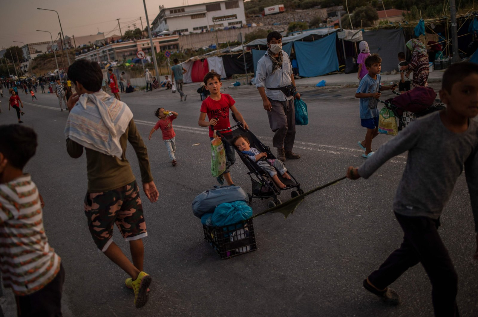 A migrant youngster drags a box carrying his belongings as he walks along a road near the Kara Tepe camp on the Greek island of Lesbos on September 15, 2020. (AFP Photo)