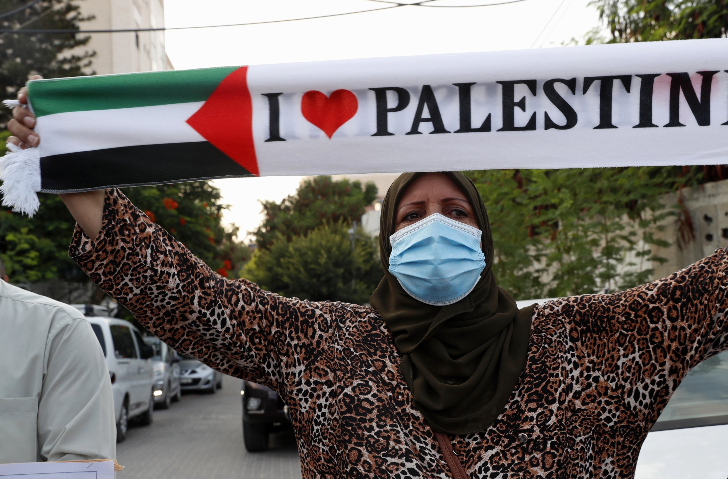 A woman wears a face mask during a protest against the United Arab Emirates and Bahraini normalization agreement with Israel, Gaza City, Sept. 15, 2020. (AP Photo)