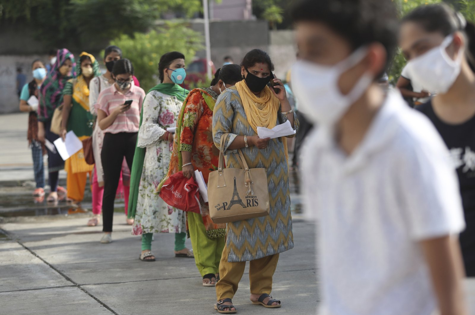 People wait in a queue to register their names to have their nasal swab samples taken to test for COVID-19 at a government hospital in Jammu, India, Sept. 15, 2020. (AP Photo)