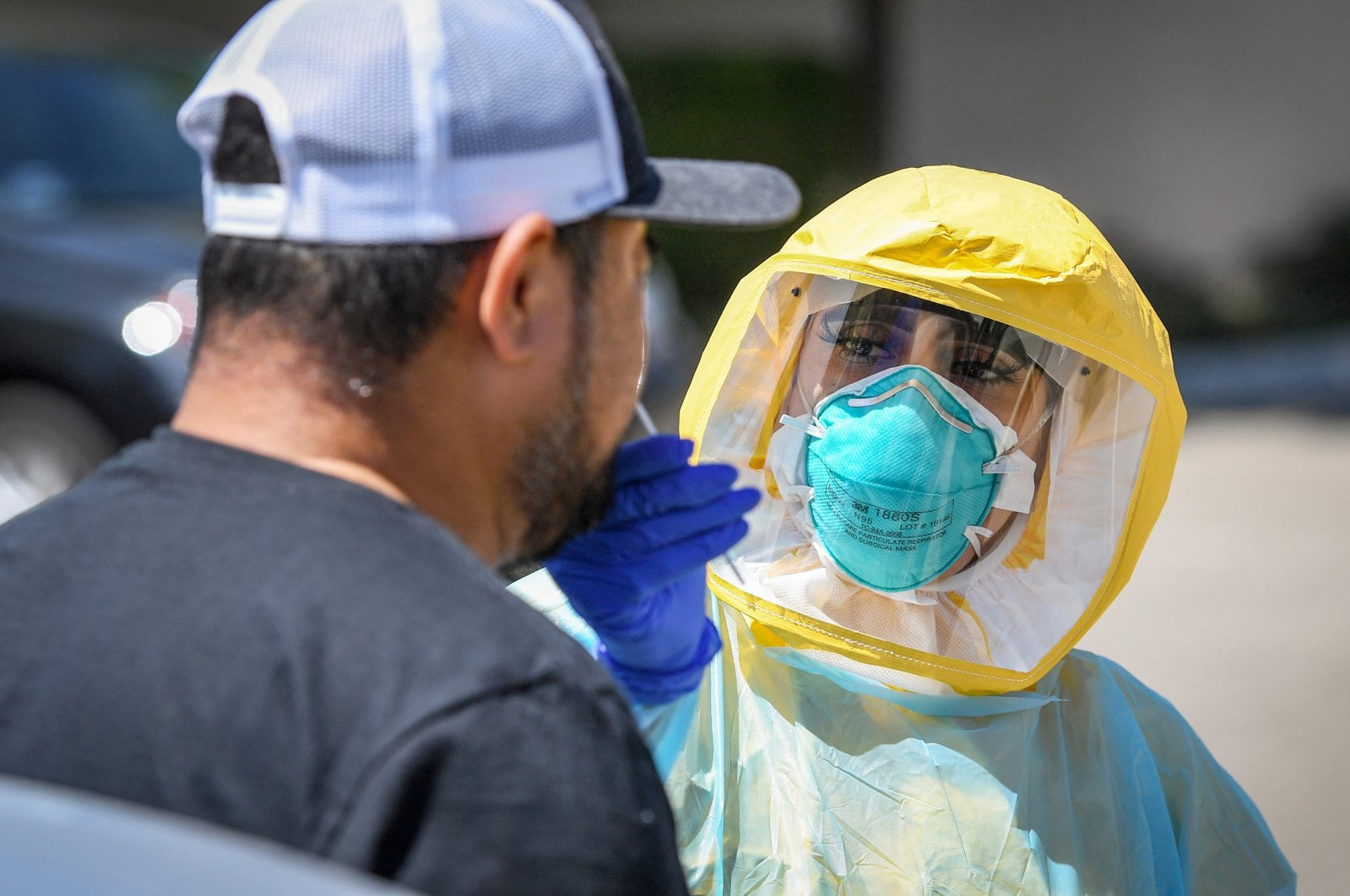 Certified medical assistant Selina Gomez from Clinica Sierra Vista in Fresno, tests a patient for COVID-19 at the drive-up testing area at the facility, Aug. 8, 2020. (CRAIG KOHLRUSS/The Fresno Bee/TNS/ABACAPRESS.COM via REUTERS)