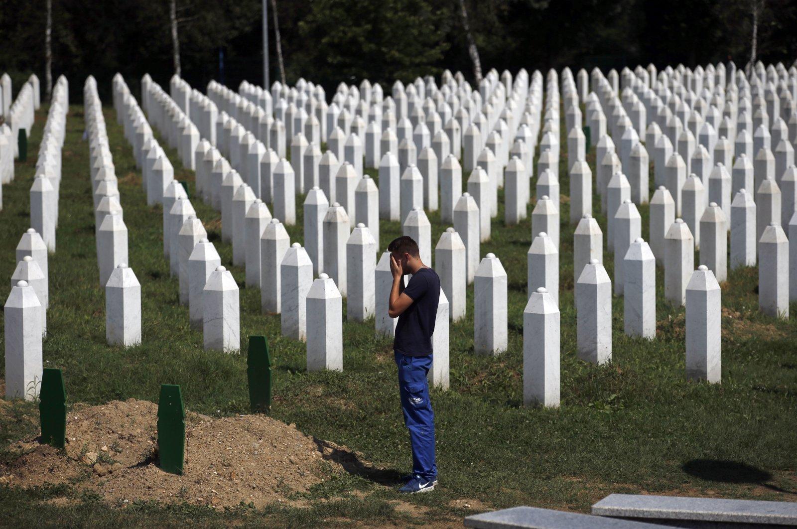 A man prays among gravestones at the memorial centre of Potocari near Srebrenica, 150 kms north east of Sarajevo, Bosnia-Herzegovina, Aug. 14, 2018. AP Photo)