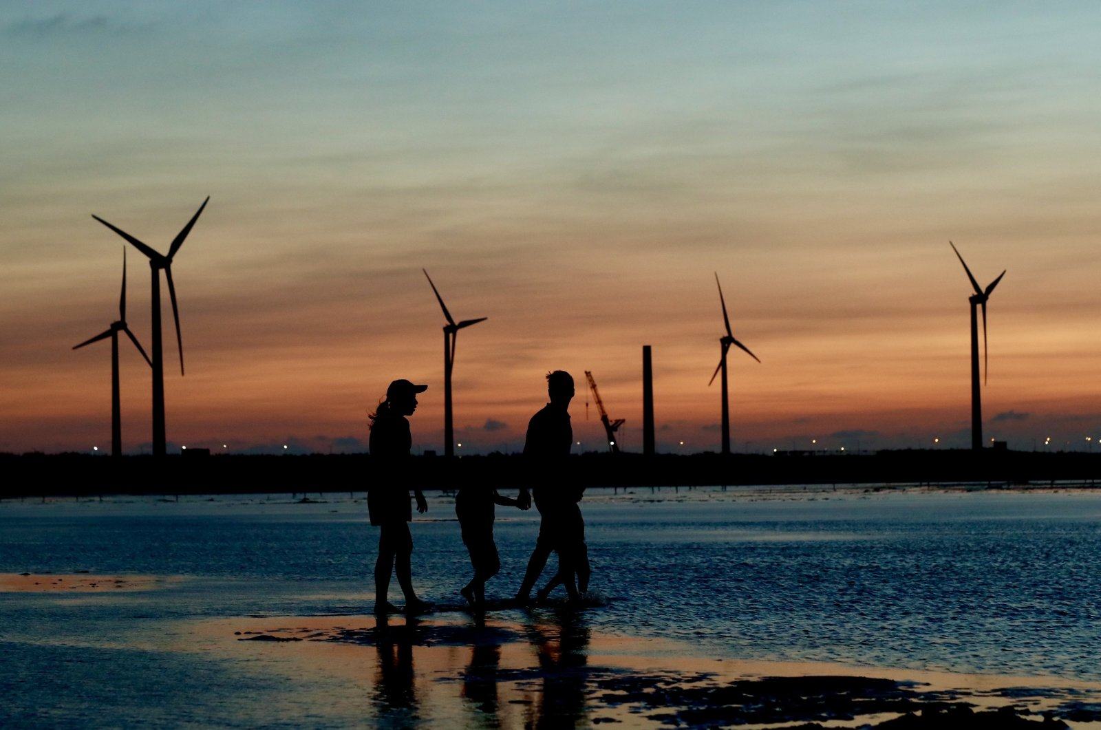 People walk next to wind turbines at sunset in Taichung, Taiwan, Sept. 15, 2020. (EPA File Photo)