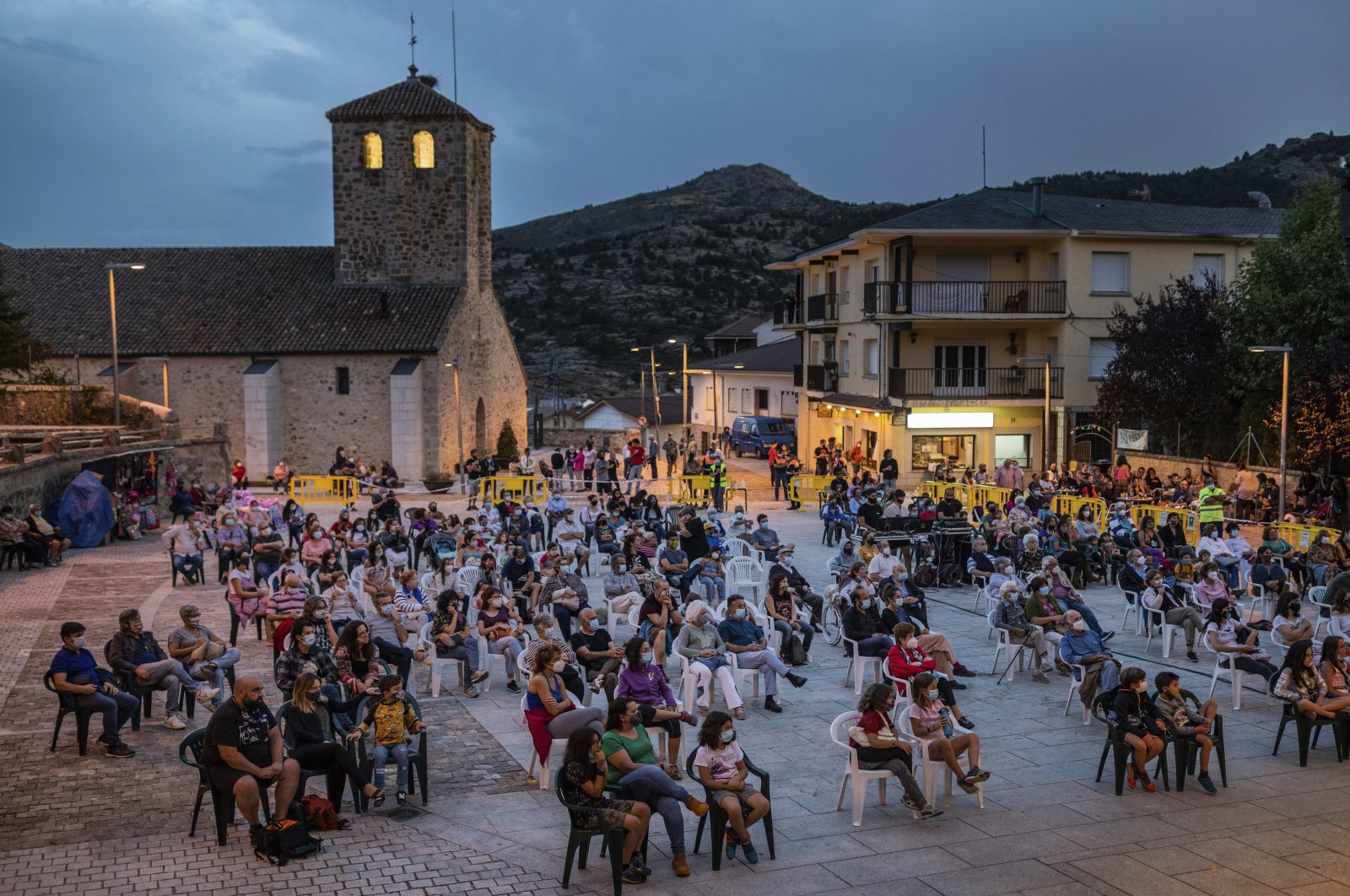 Spectators wearing face masks and keeping social distance to protect against the coronavirus attend an entertainment show in the village of Bustarviejo in the outskirts of Madrid, Spain, Sept. 14, 2020. (AP Photo)