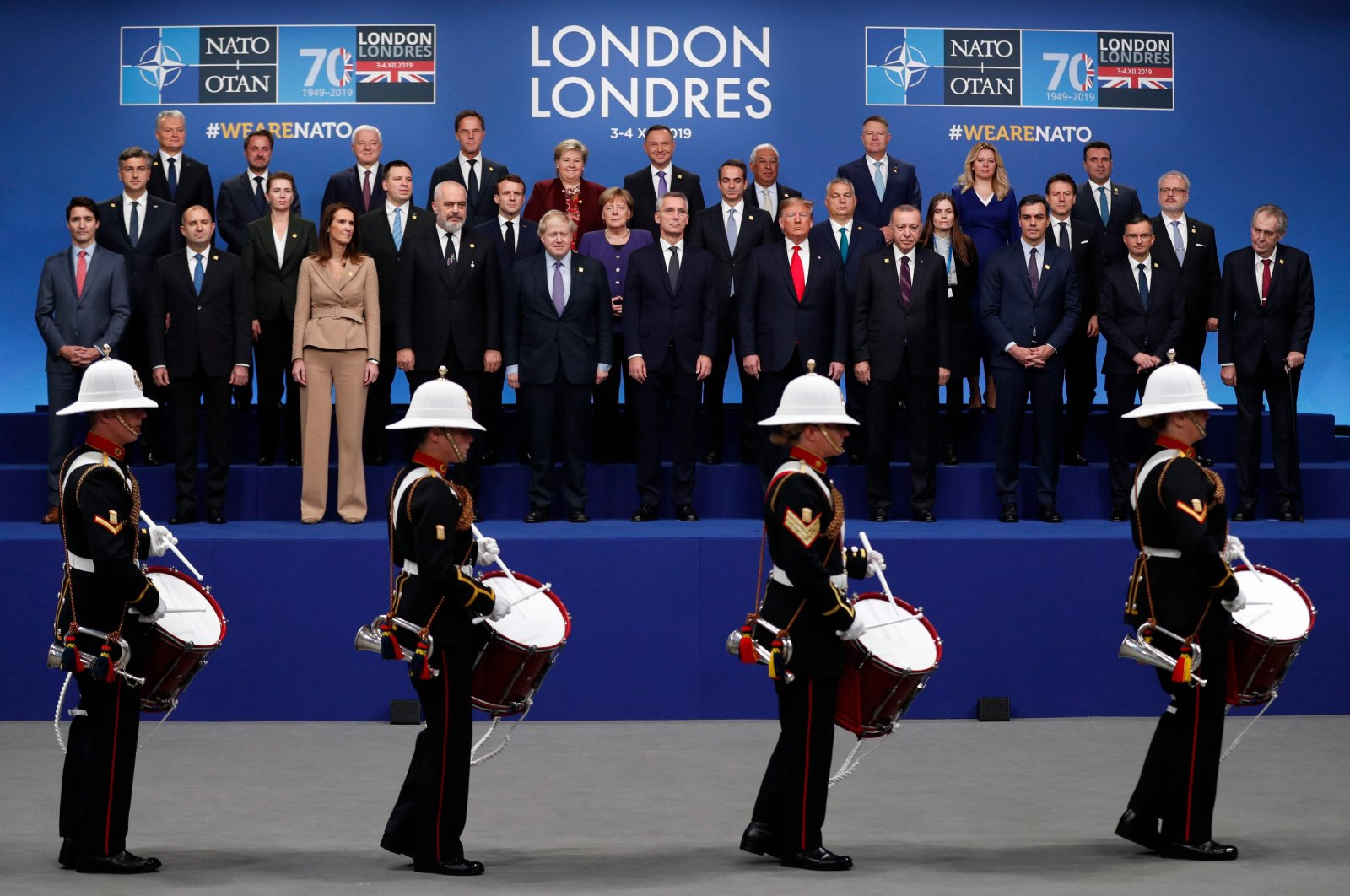 Heads of government watch a marching band perform as they pose for a family photo at the NATO summit at the Grove hotel in Watford, northeast of London, Dec. 4, 2019. (AFP Photo)