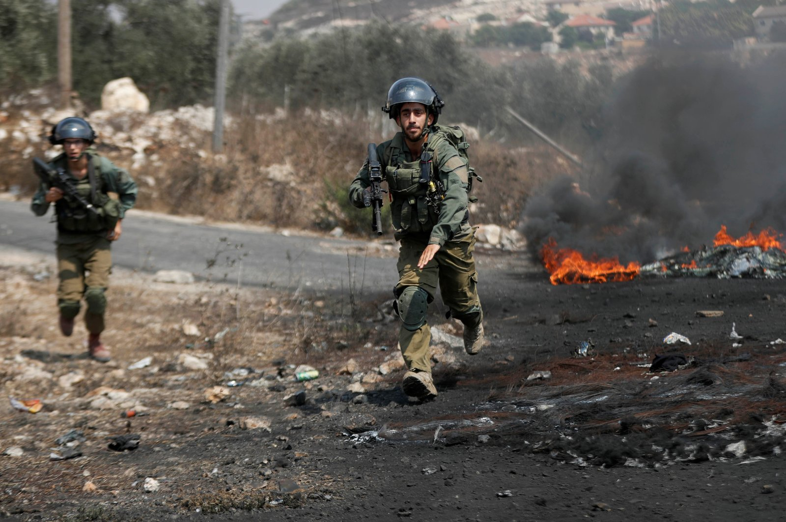 Israeli soldiers run toward demonstrators during a Palestinian protest against Israeli violence, in Kafr Qaddum town in the Israeli-occupied West Bank, Sept.11, 2020. (Reuters Photo)