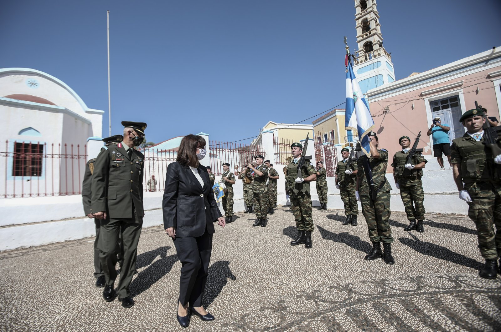 In this photo provided by the Greek President's office on Sunday, Sept. 13, 2020, Greece's President Katerina Sakellaropoulou inspects a guard of honour during celebrations marking when the southeastern island of Kastellorizo, formally became part of Greece. (Greek President's Office via AP)