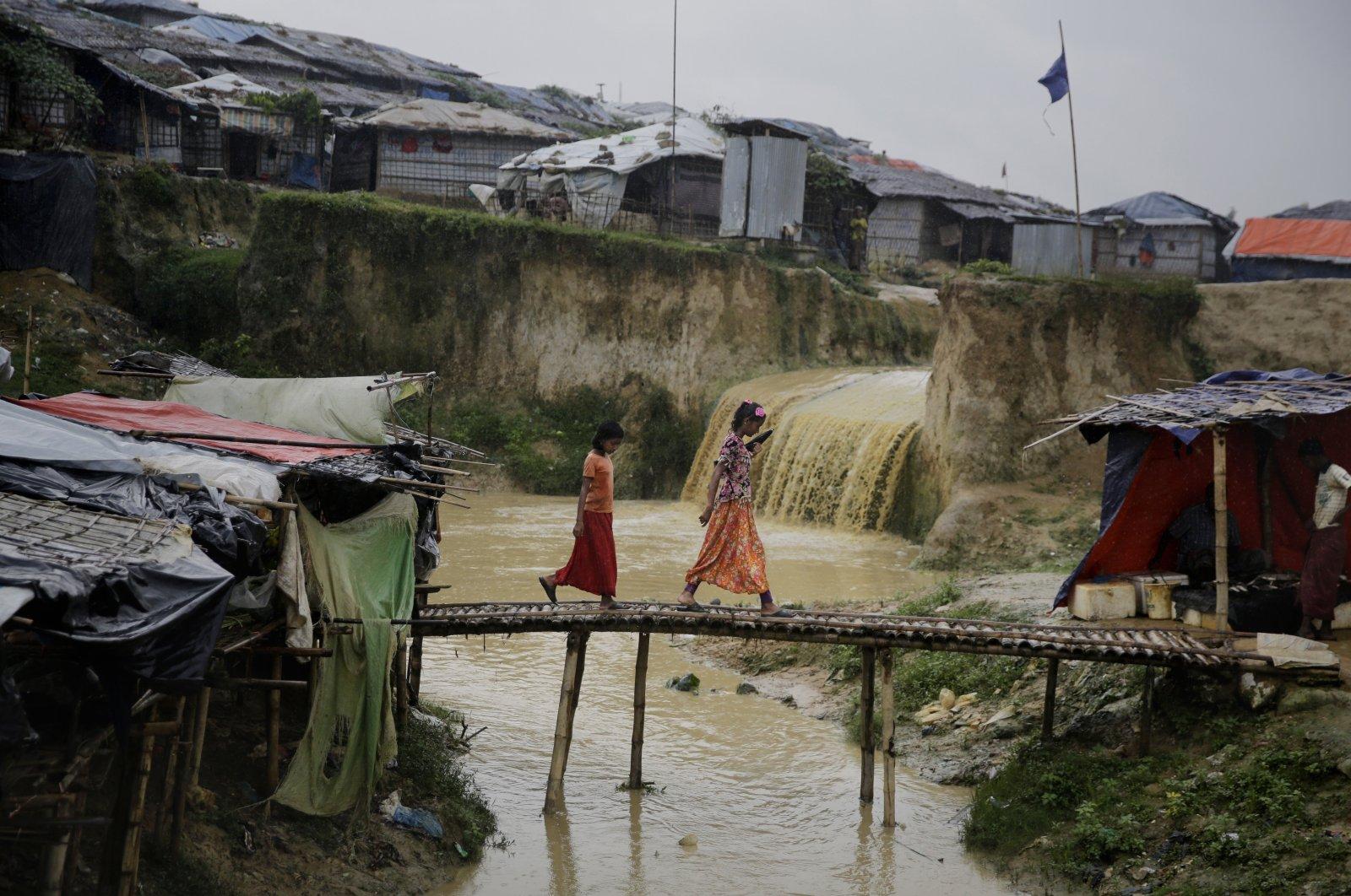 Rohingya refugee girls cross a makeshift bamboo bridge at Kutupalong refugee camp, Bangladesh, Aug. 28, 2018. (AP Photo)