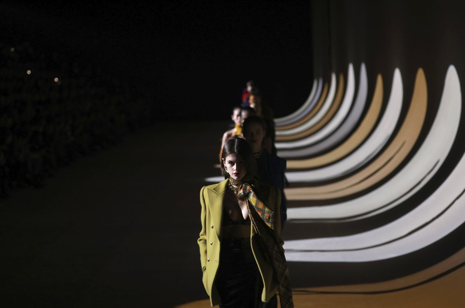 In this Feb. 25, 2020 file photo, model Kaia Gerber leads other models as they wear creations for the Saint Laurent fashion collection during Women's fashion week Fall/Winter 2020/21 presented in Paris. (AP Photo)