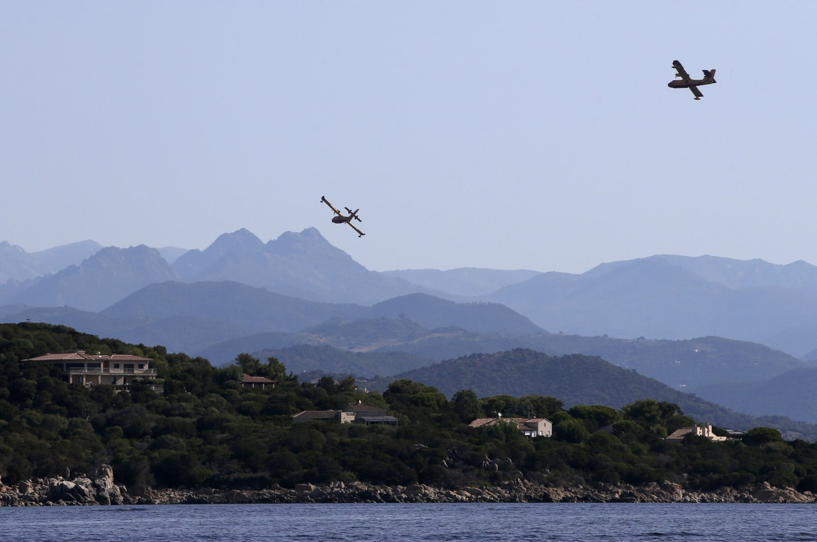 Two Canadair CL-415 firefighting planes of the French Securite Civile fly over Porto-Pollo on the French Mediterranean island of Corsica, Aug. 21, 2020. (AFP Photo)