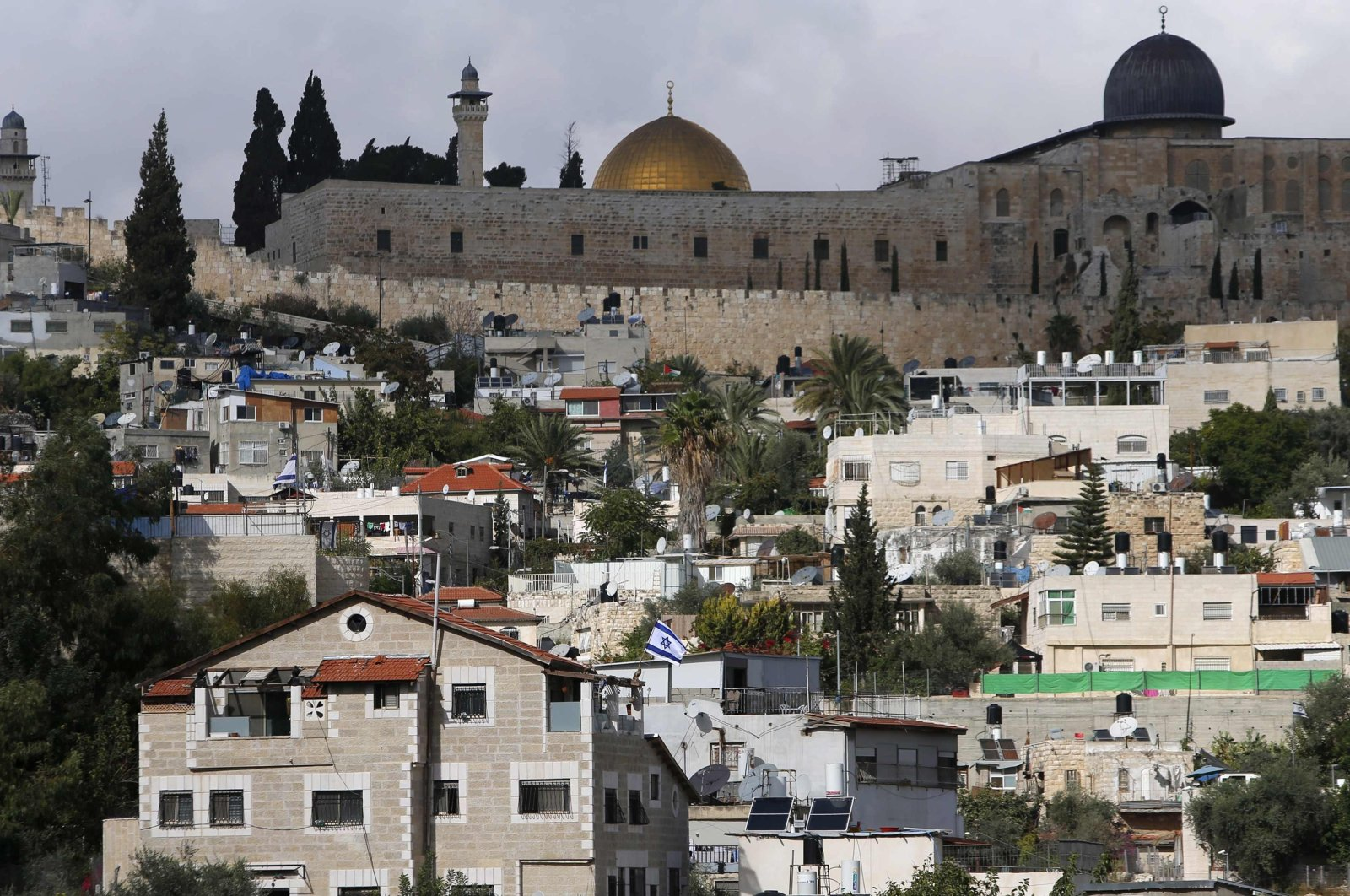 The Dome of the Rock and Al-Aqsa Mosque are seen in background as an Israeli flag flutters from atop a home of Jewish settlers in Silwan, a mostly Palestinian district abutting the Old City, Nov. 3, 2014. (Reuters Photo)
