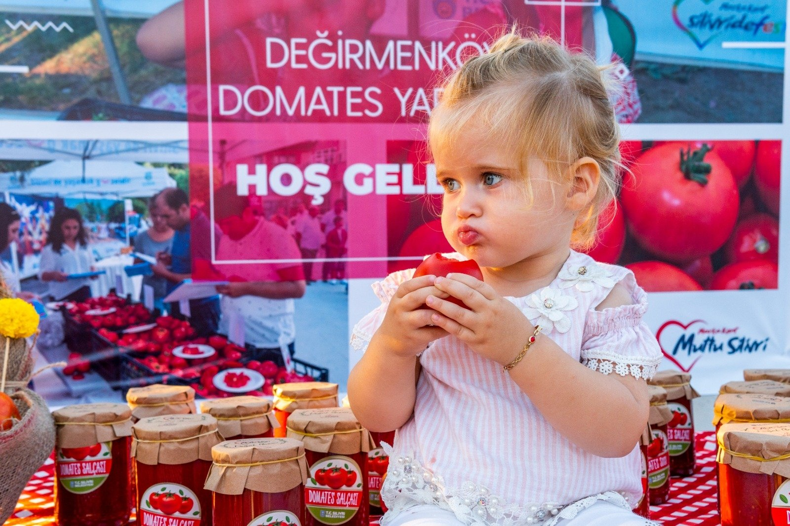 A young girl enjoys a freshly picked tomato in Silivri, Istanbul, Aug. 24, 2020. (DHA Photo)