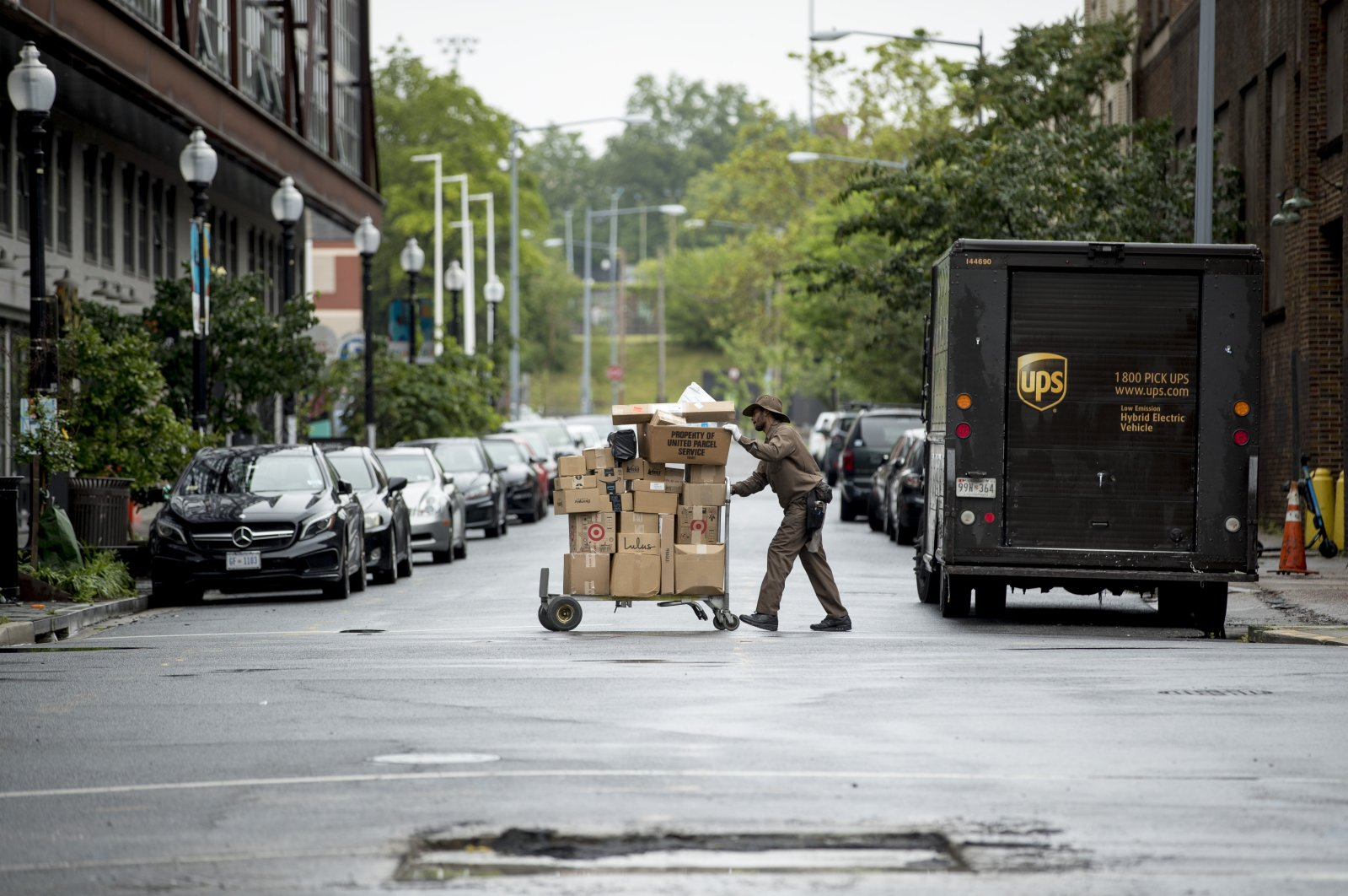 A delivery man pushes a cart full of packages to deliver to an apartment building on an almost empty street in the Shaw neighborhood of Washington, D.C., U.S., May 22, 2020. (AP Photo)