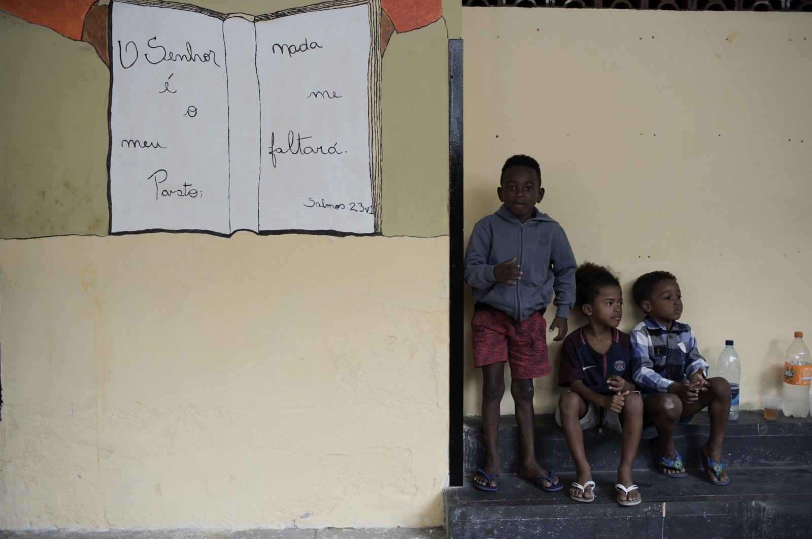 Children wait as their parents move their belongings from a house they occupied before being evicted amid the coronavirus pandemic in Rio de Janeiro, Brazil, Sept.15, 2020. (AP Photo)
