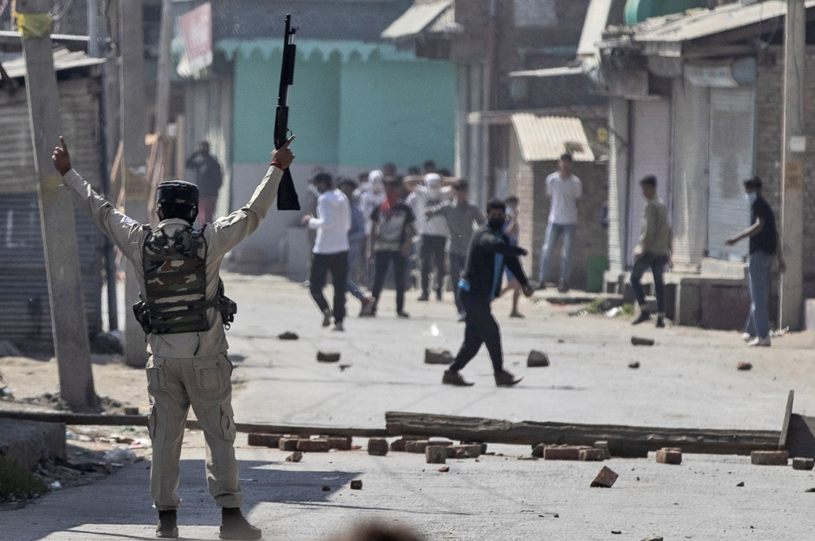 An Indian paramilitary soldier holds up a pellet gun as he challenges Kashmiri protesters marching on the streets in solidarity with rebels engaged in a gunbattle with soldiers, in Srinagar, Indian-controlled Kashmir, Sept. 17, 2020. (AP Photo)