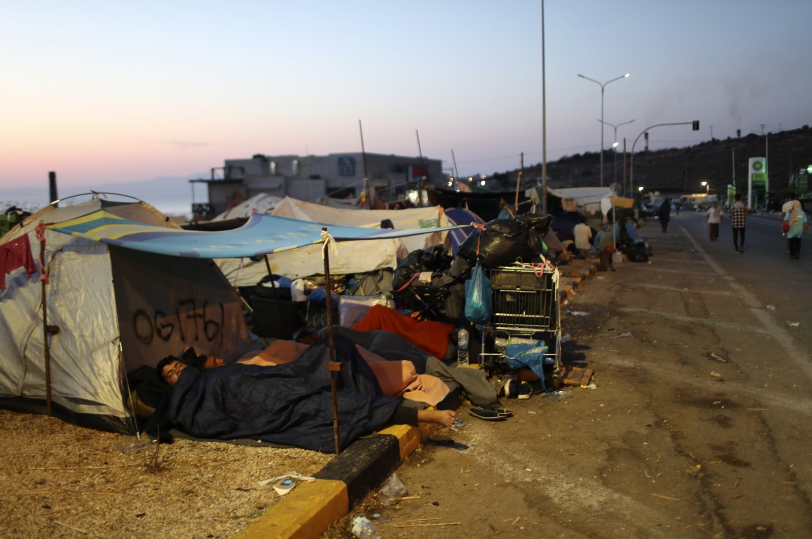 Migrants sleep outside their tents as they remain camped out on a road leading from Moria to the capital of Mytilene, Lesbos, Sept. 17, 2020. (AP Photo)
