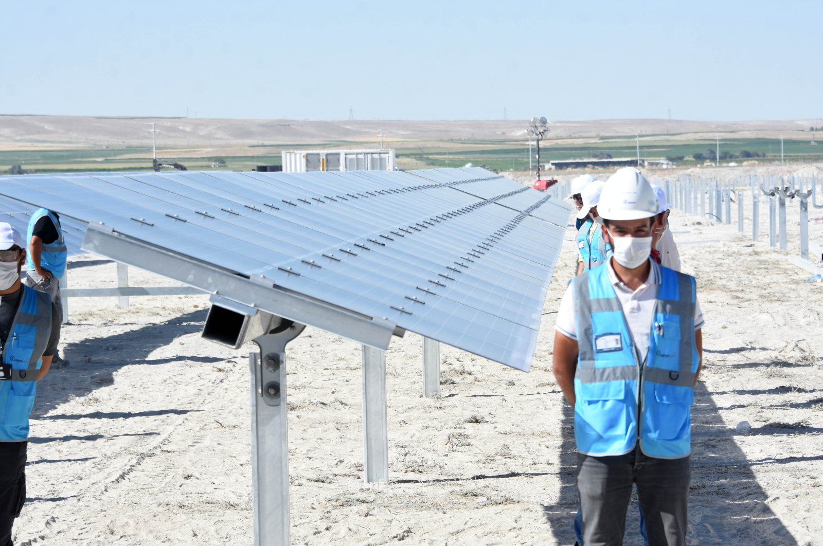 Workers stand by the solar panels in central Turkey's Karapınar SSP during the inauguration ceremony on Aug. 19, 2020. (DHA Photo)