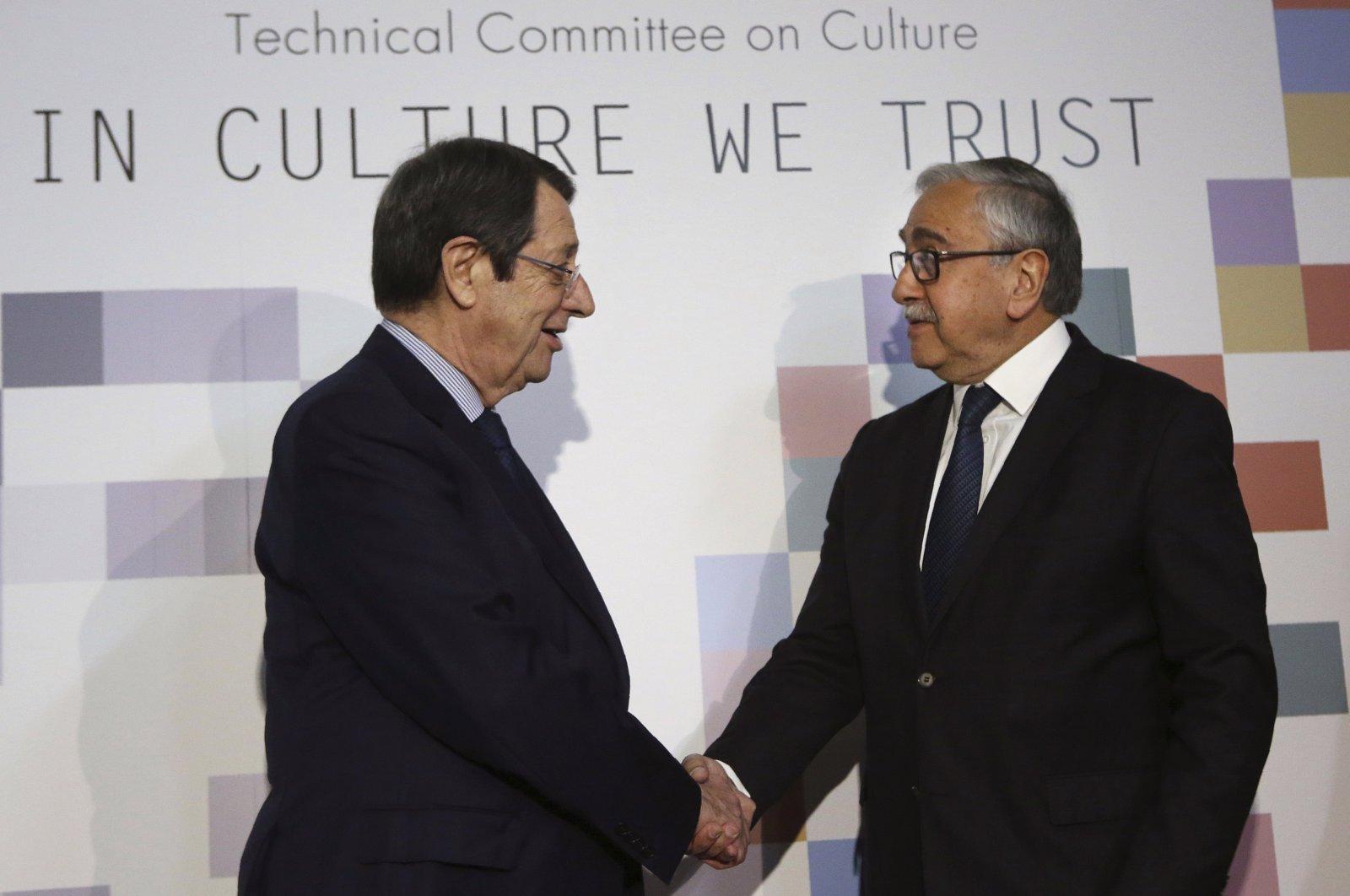 Greek Cypriot leader Nicos Anastasiades, left, and Turkish Cypriot President Mustafa Akıncı, shake hands in Nicosia, Feb. 3, 2020. (AP Photo)