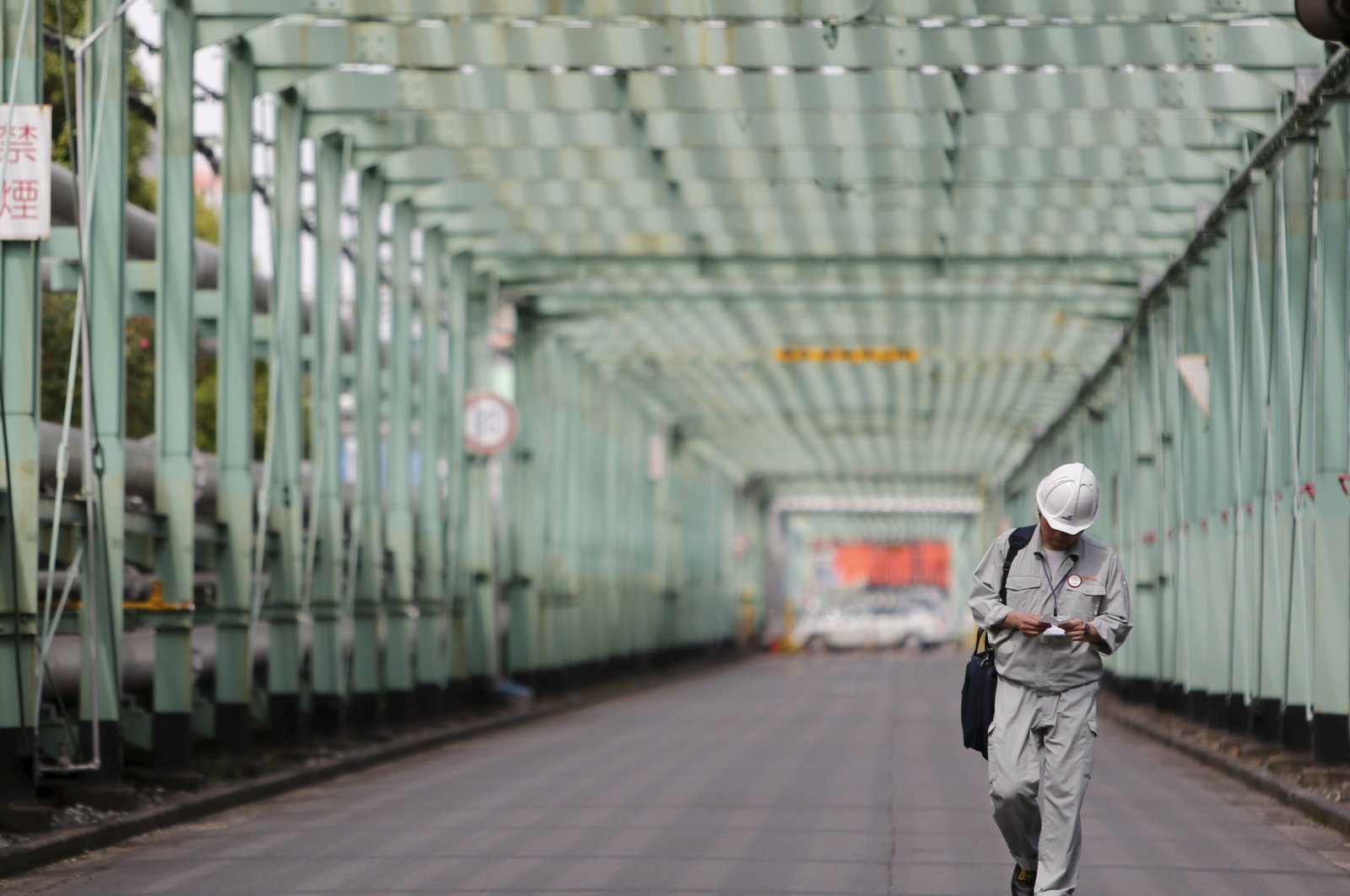 A man walks inside a factory at Keihin industrial zone in Kawasaki, south of Tokyo, Japan, June 28, 2013. (Reuters Photo)