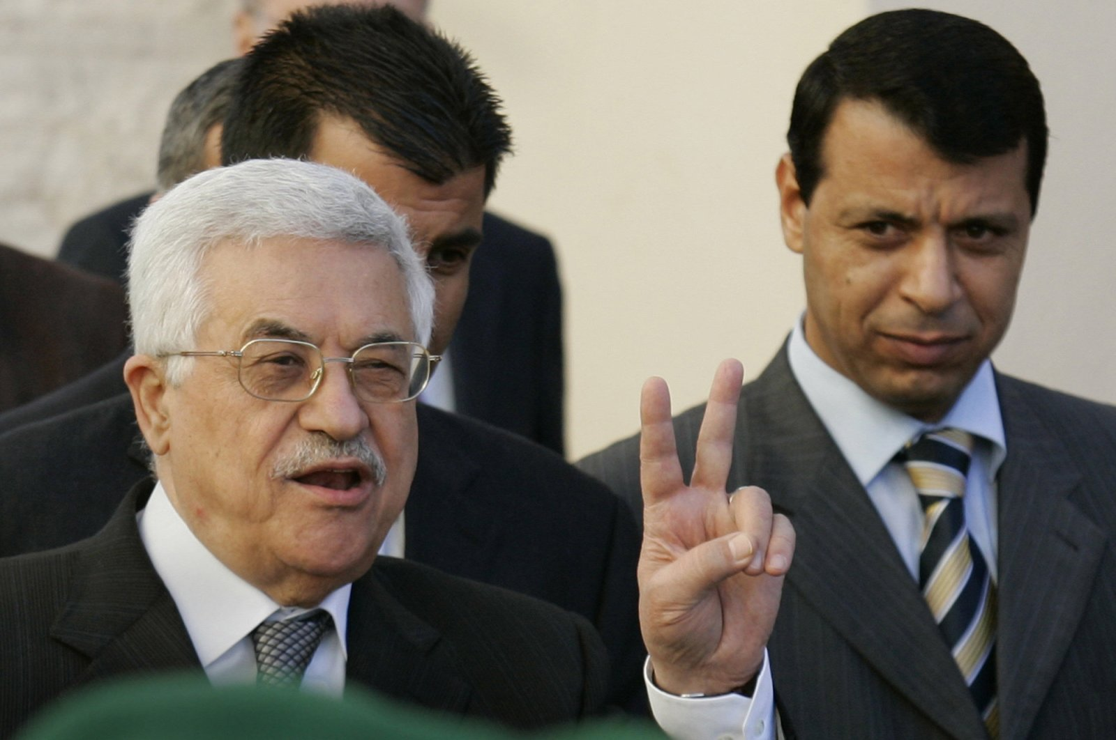 Palestinian Authority President Mahmoud Abbas (L) flashes the peace sign as Mohammed Dahlan looks on in the West Bank town of Ramallah, Dec. 18, 2006. (AP Photo)