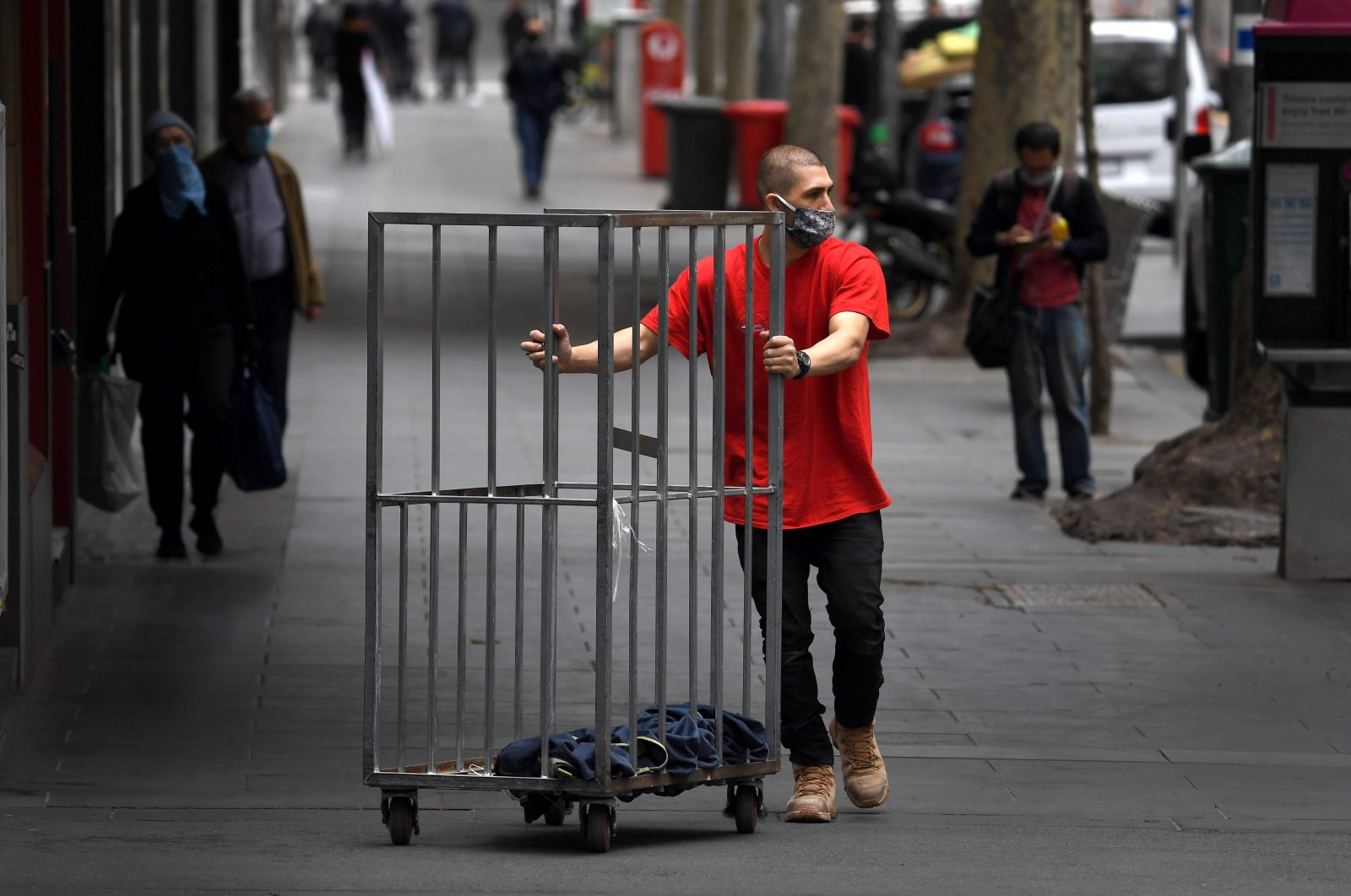 A man pushes an empty trolley along a street in Melbourne's city center, Australia, Sept. 17, 2020. (AFP Photo)