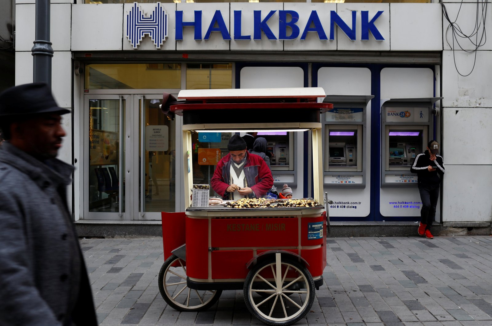 A street vendor sells roasted chestnuts in front of a branch of Halkbank in central Istanbul, Turkey, Jan. 10, 2018. (Reuters Photo)
