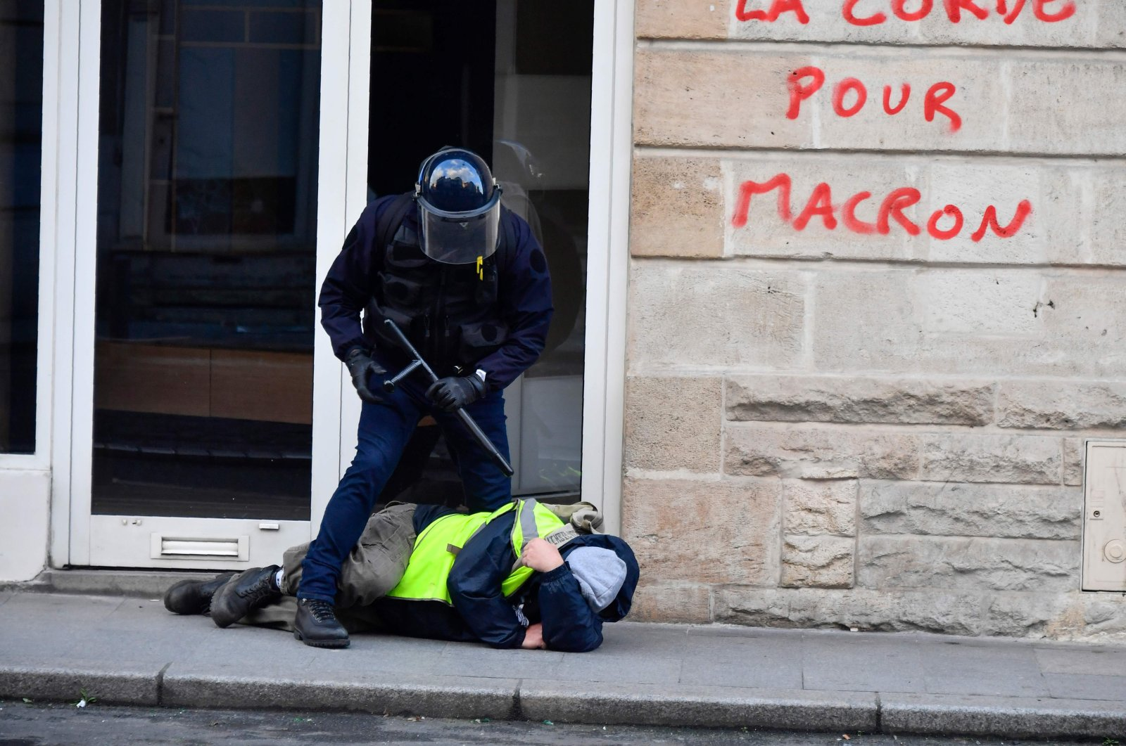 """A riot policeman stands over a protestor wearing a yellow vest during clashes with protesters in a demonstration called by the """"Yellow Vests"""" movement in Bordeaux, Feb. 2, 2019. (AFP Photo)"""