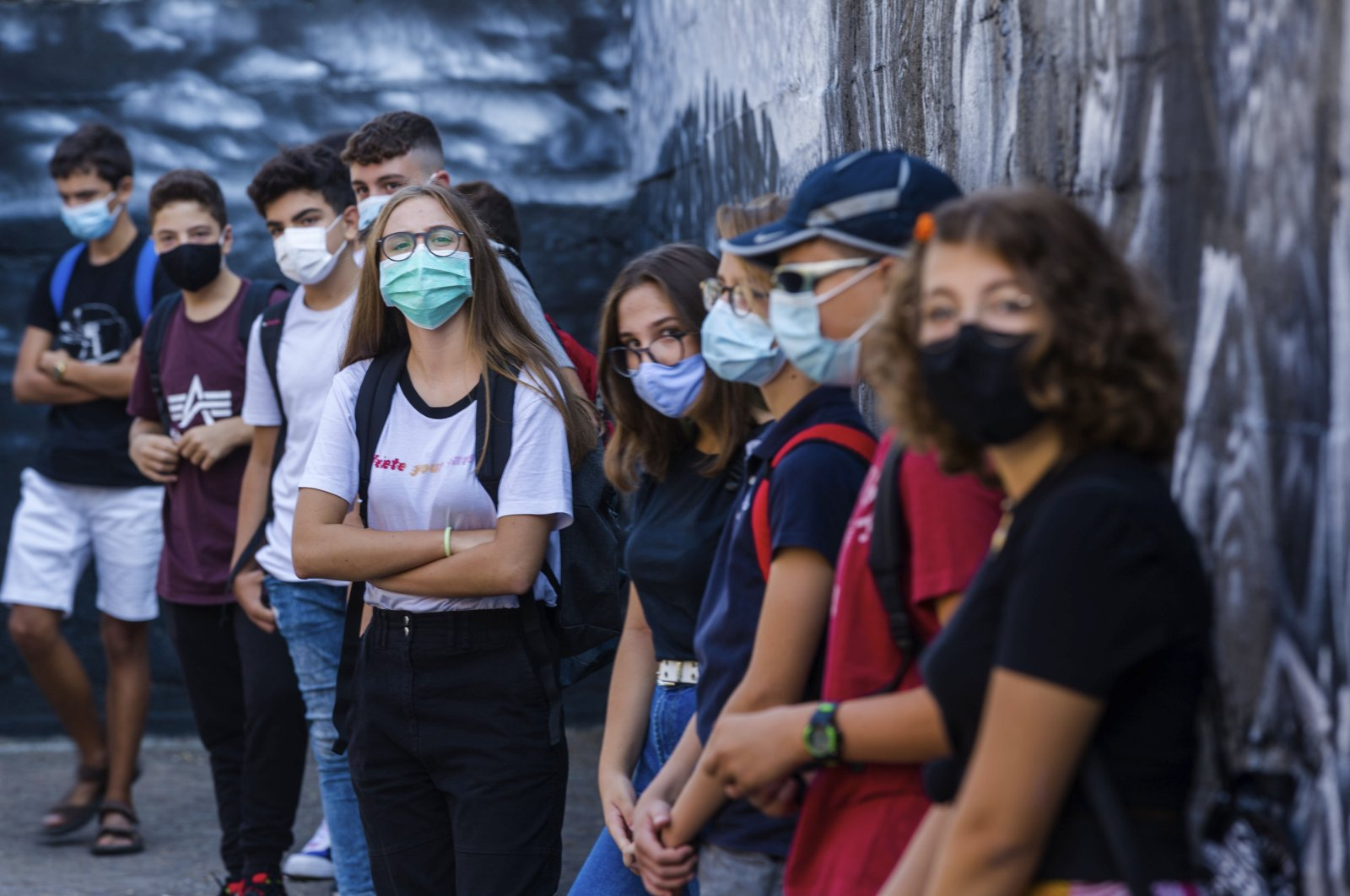 Pupils listen to teachers briefing them on the anti-COVID19 guidelines before they start their first day of school at the high school Giovanni Battista Morgagni in Rome, Monday, Sept. 14, 2020. (AP Photo)