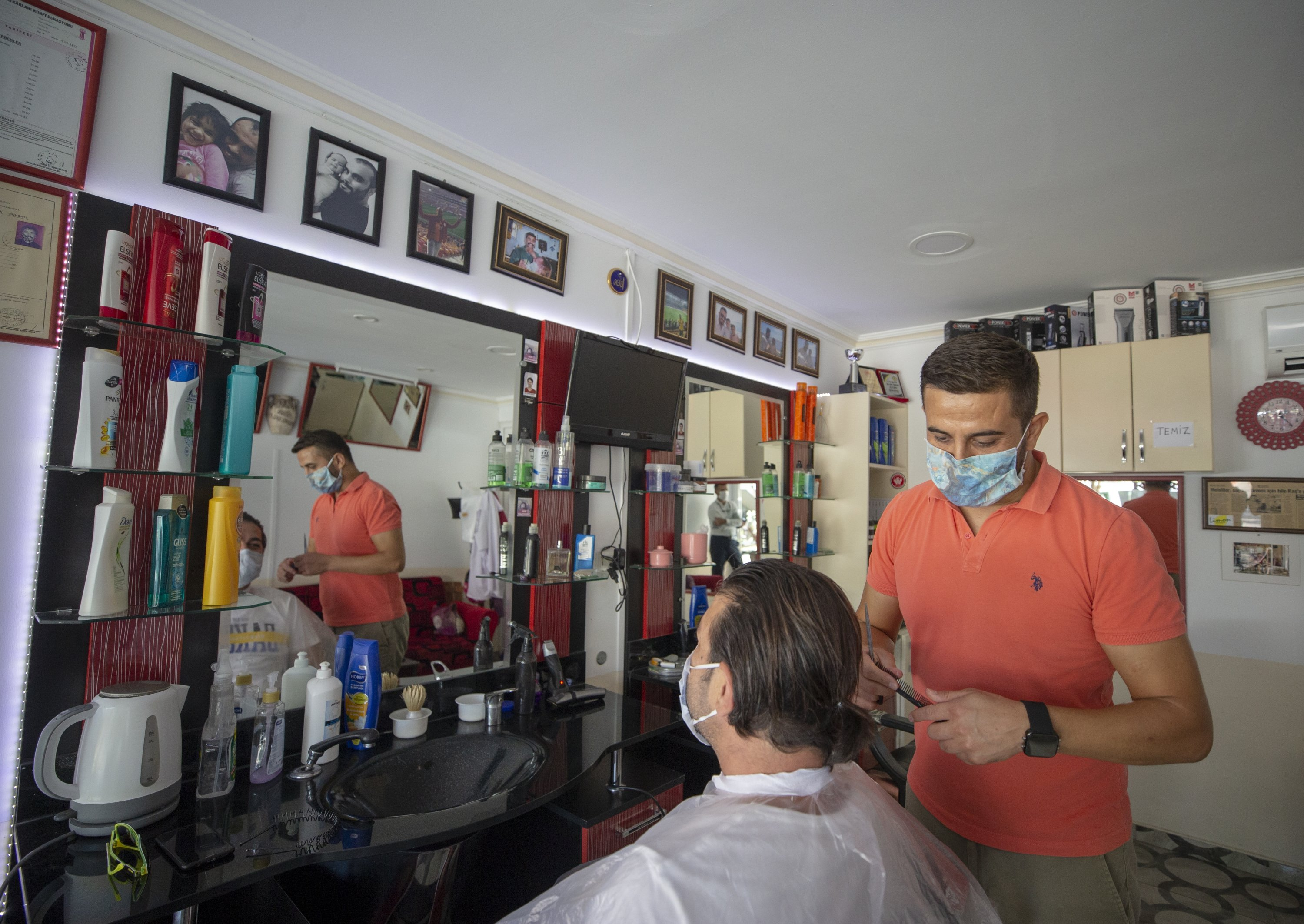 Bayram Aydoğdu, who has been keeping in touch with his friends in Kastellorizo through videoconferences, works at his barbershop in Kaş, Antalya province, southern Turkey, Sept. 18, 2020. (AA Photo)