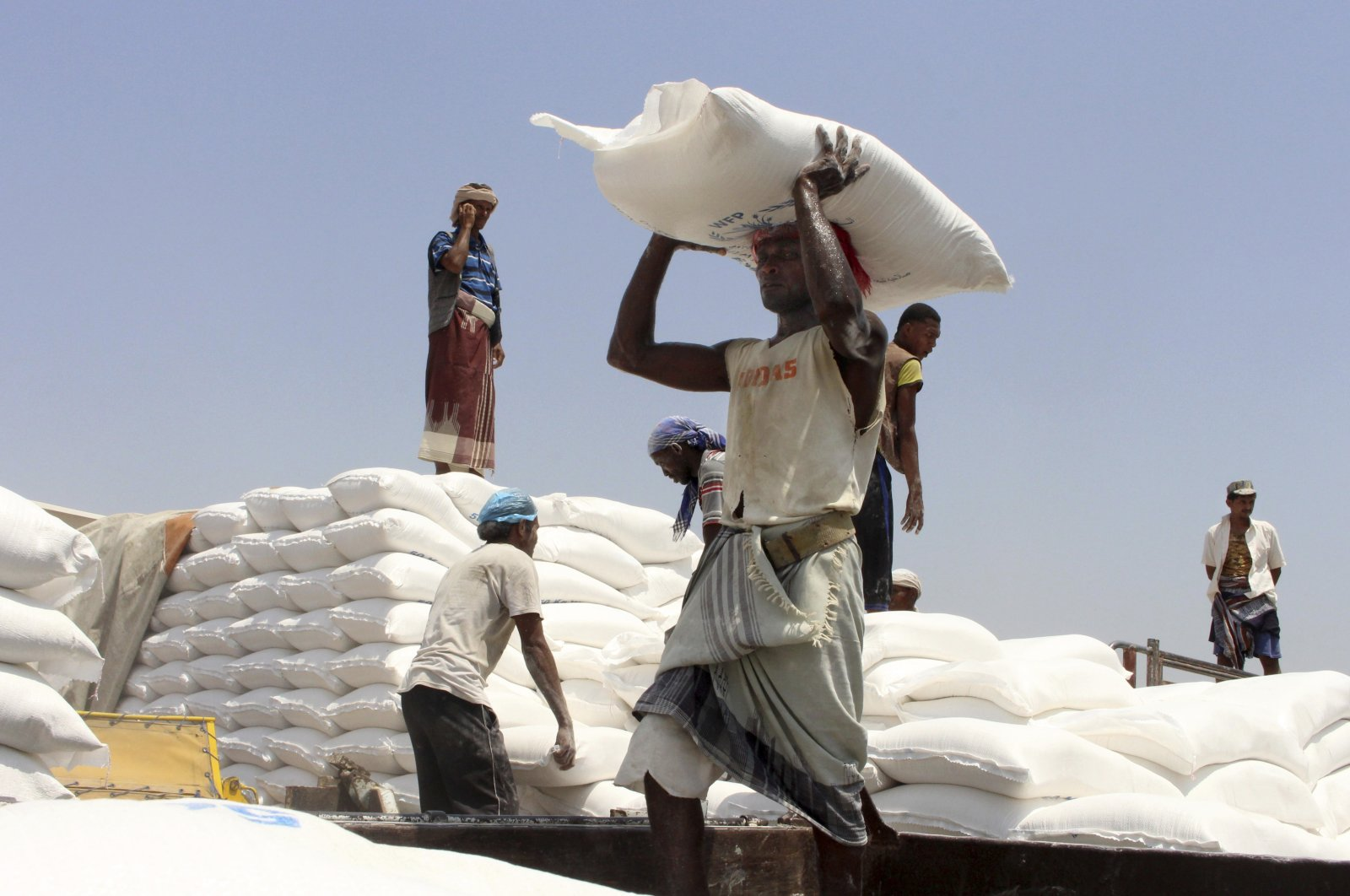 In this file photo, men deliver U.N. World Food Programme (WFP) aid in Aslam, Hajjah, Yemen on Sept. 21, 2018. (AP Photo)