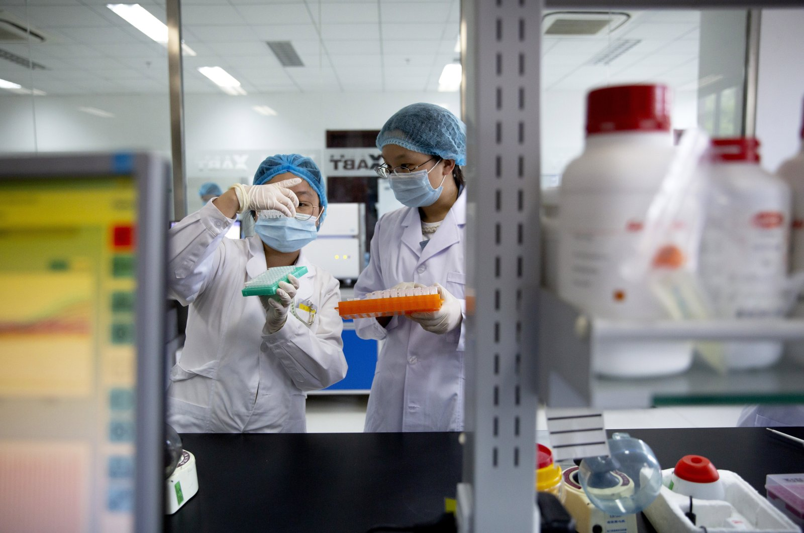 Employees work in a research and development lab of Beijing Applied Biological Technologies, a firm which is developing COVID-19 molecular diagnostic test kits, during a government-organized tour for journalists in Beijing, China, May 14, 2020. (AP Photo)