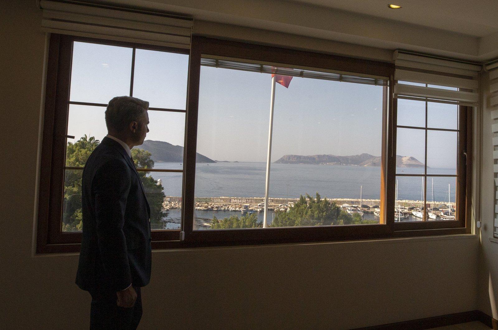 Kaş District Governor Şaban Arda Yazıcı looks at the island of Kastellorizo from the window of his office in Kaş, Antalya province, southern Turkey, Sept. 18, 2020. (AA Photo)