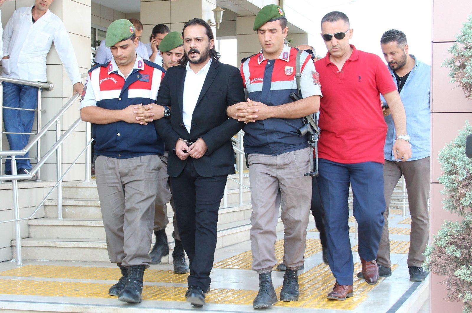 Writer Emrah Serbes is escorted out of a court by gendarmerie officers in Izmir, Turkey, in this undated photo. (IHA Photo)