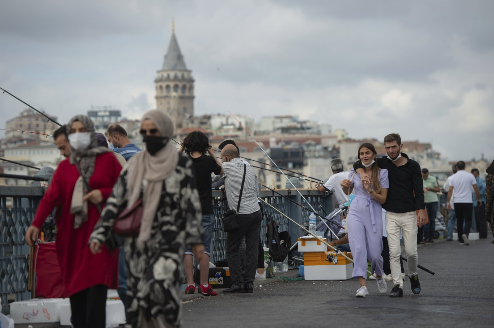 Backdropped by Istanbul's iconic Galata Tower, people wearing masks for protection against the spread of coronavirus, walk over Eminonu bridge in Istanbul, Sept. 11, 2020. (AP Photo)