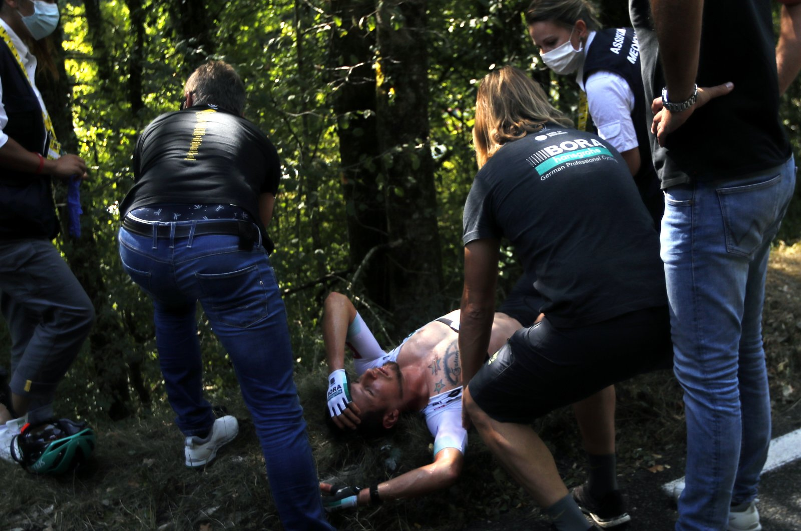 Lukas Postlberger of Austria is treated by medics during stage 19 of the Tour de France cycling race over 166 kilometers (103 miles), with the start in Bourg-en-Bresse and finish in Champagnole, France, Sept. 18, 2020. (AP Photo)