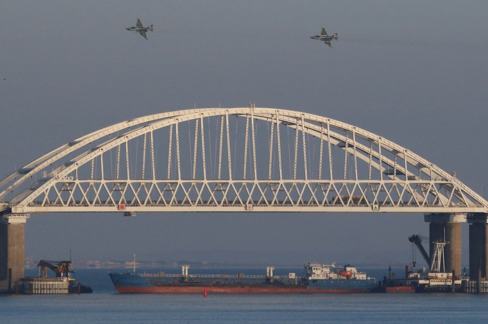 Russian jet fighters fly over a bridge connecting the Russian mainland with the Crimean Peninsula with a cargo ship beneath it after three Ukrainian navy vessels were stopped by Russia from entering the Sea of Azov via the Kerch Strait in the Black Sea, Crimea on Nov. 25, 2018. (Reuters Photo)