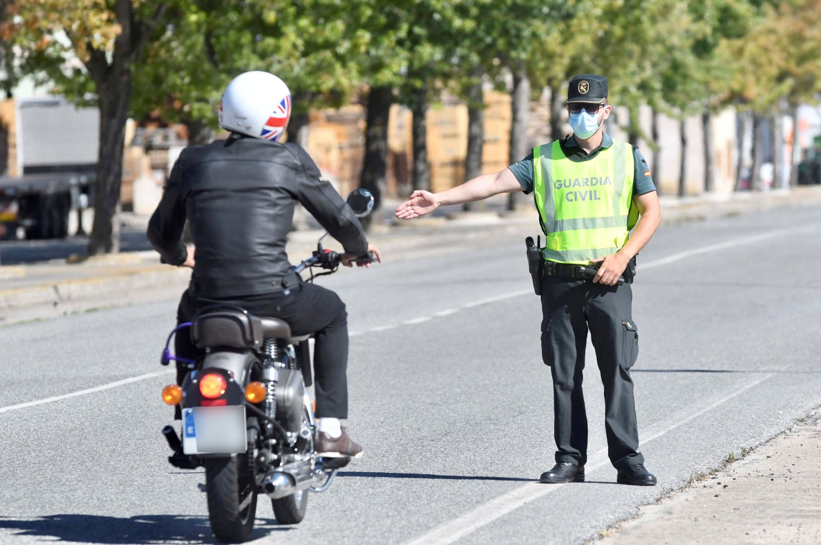 A Civil Guard officer (R) stops a rider as he controls the exit and entry in the village of Cantalejo, Spain, Aug 22, 2020.